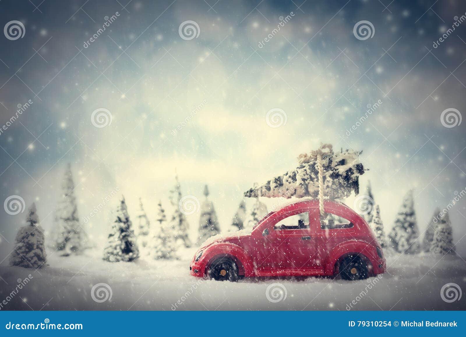 Retro stuk speelgoed auto die uiterst kleine Kerstboom dragen Fairytalelandschap met sneeuw en bos