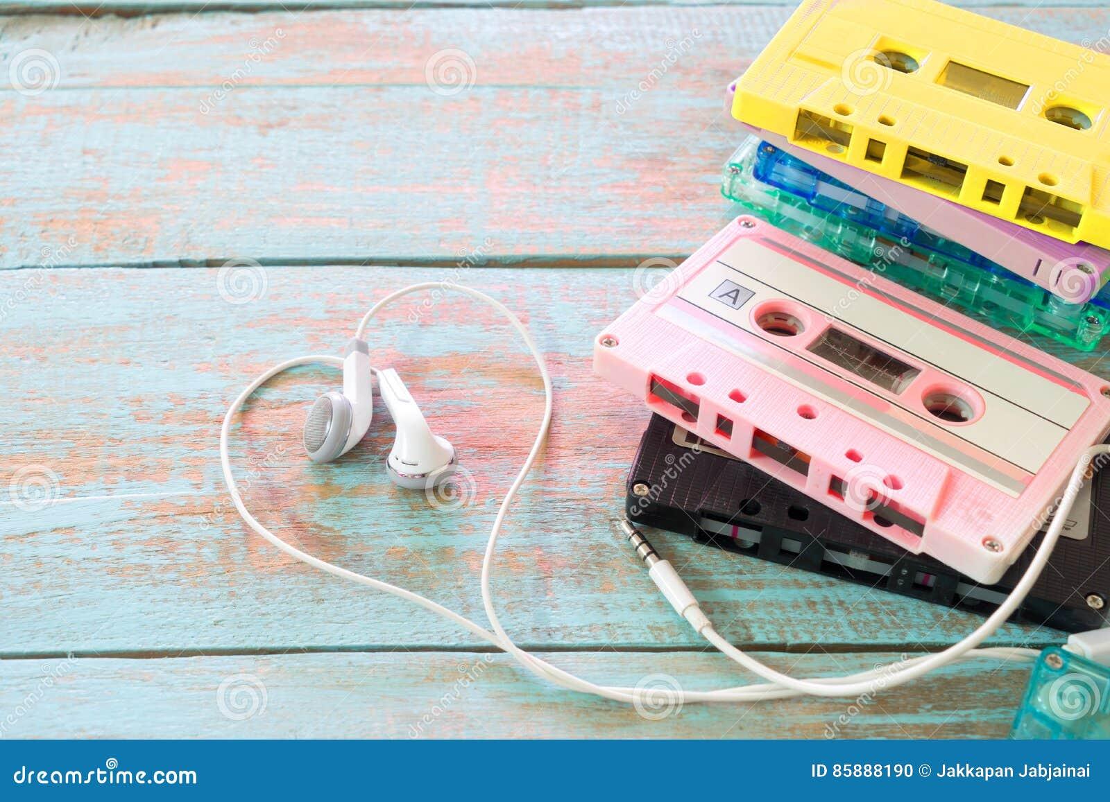 Retro tape cassette with earphone heart shape on wood table.
