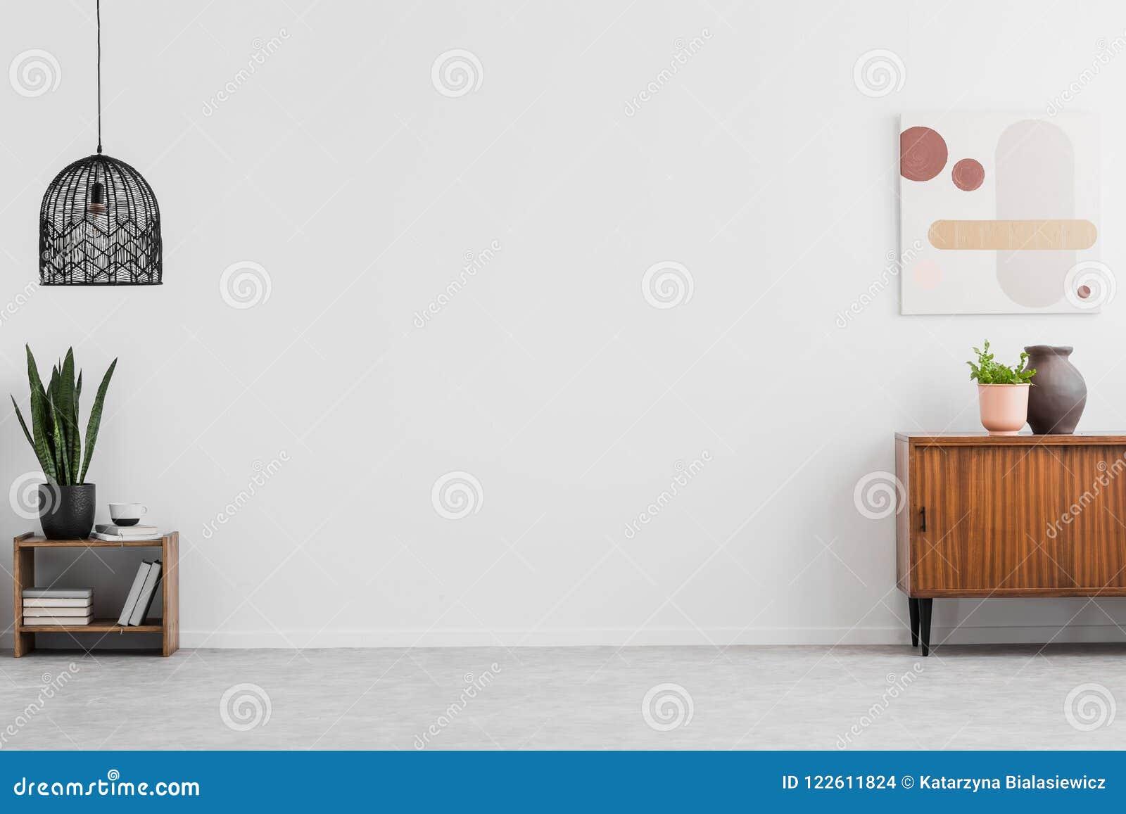 Retro träkabinett och en målning i en tom vardagsruminre med vita väggar och kopieringsutrymmeställe för en soffa Verkligt foto