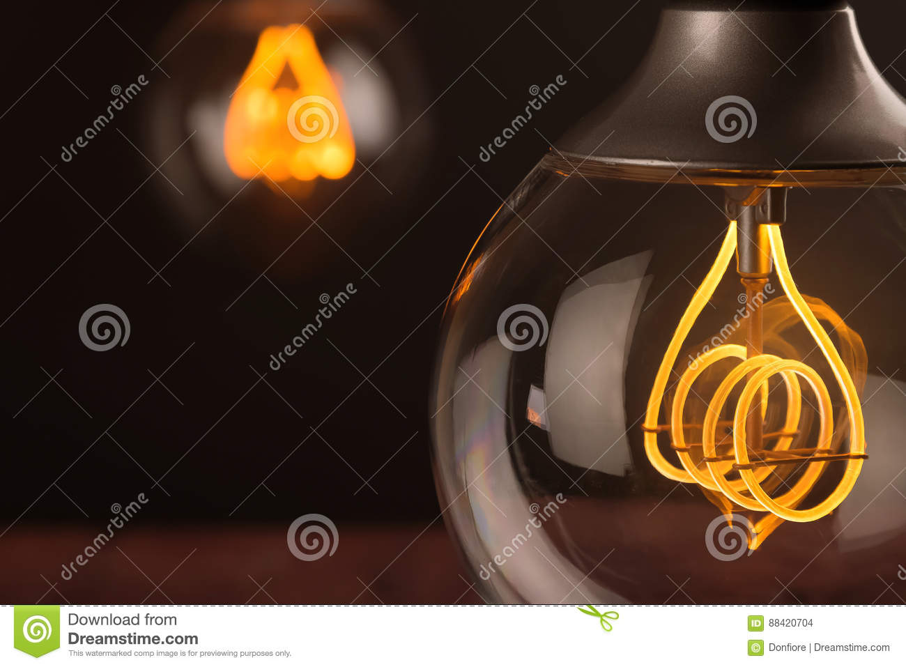 Retro vintage light bulb with led technology bult-in on warm light yellow tint and black background, energy saving with old style