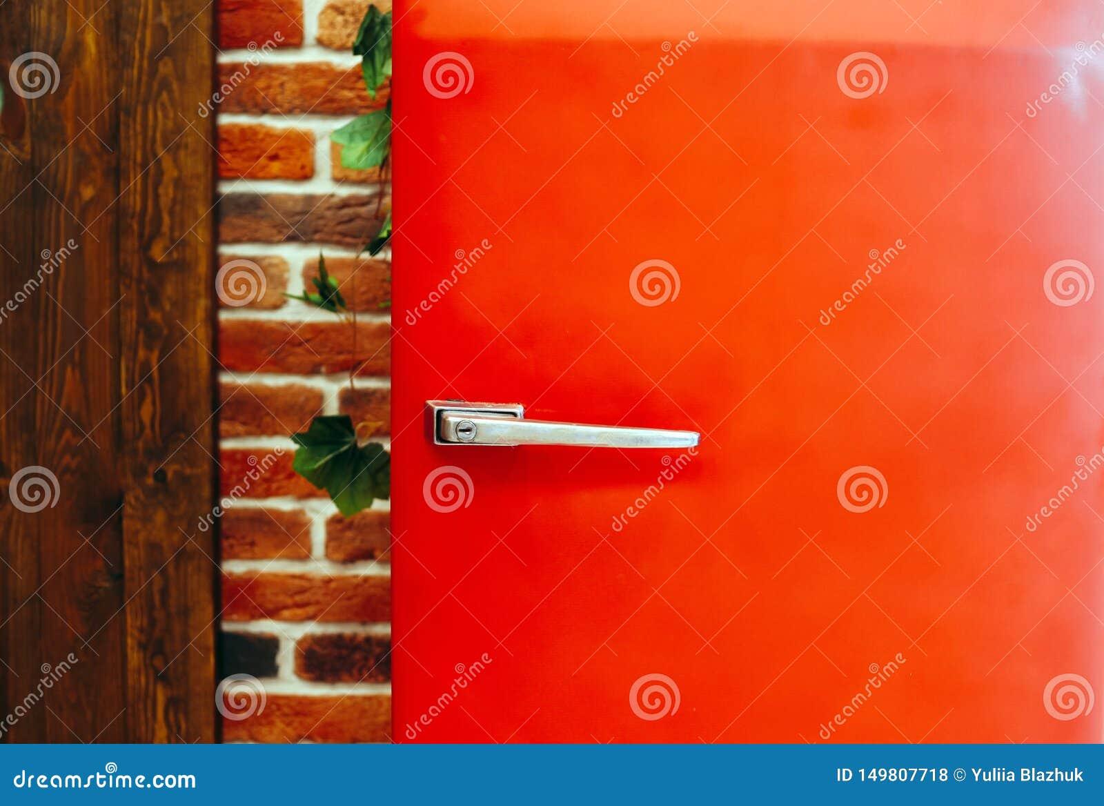 Retro vintage style red fridge against brick wall background