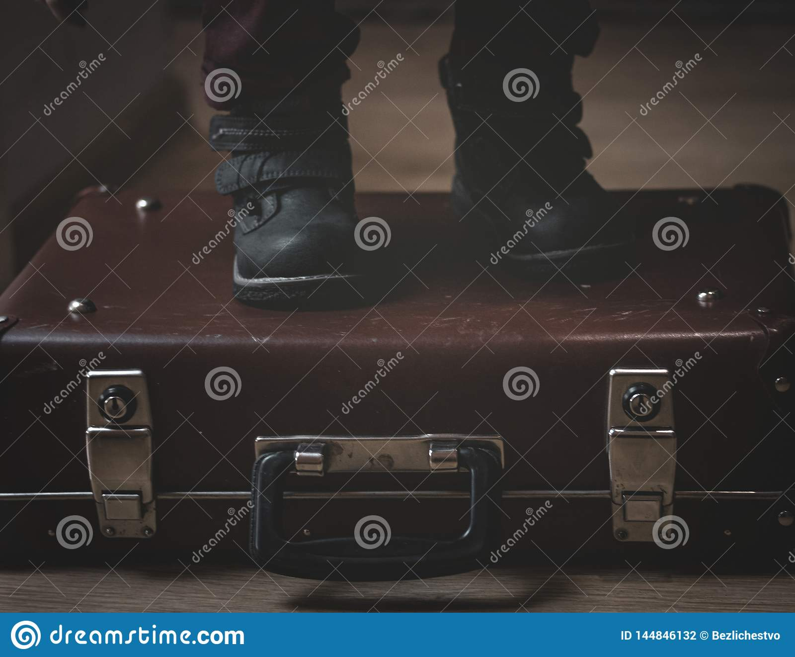 On a retro vintage burgundy brown suitcase are the feet of a child in shoes. Low key. Matte shadows