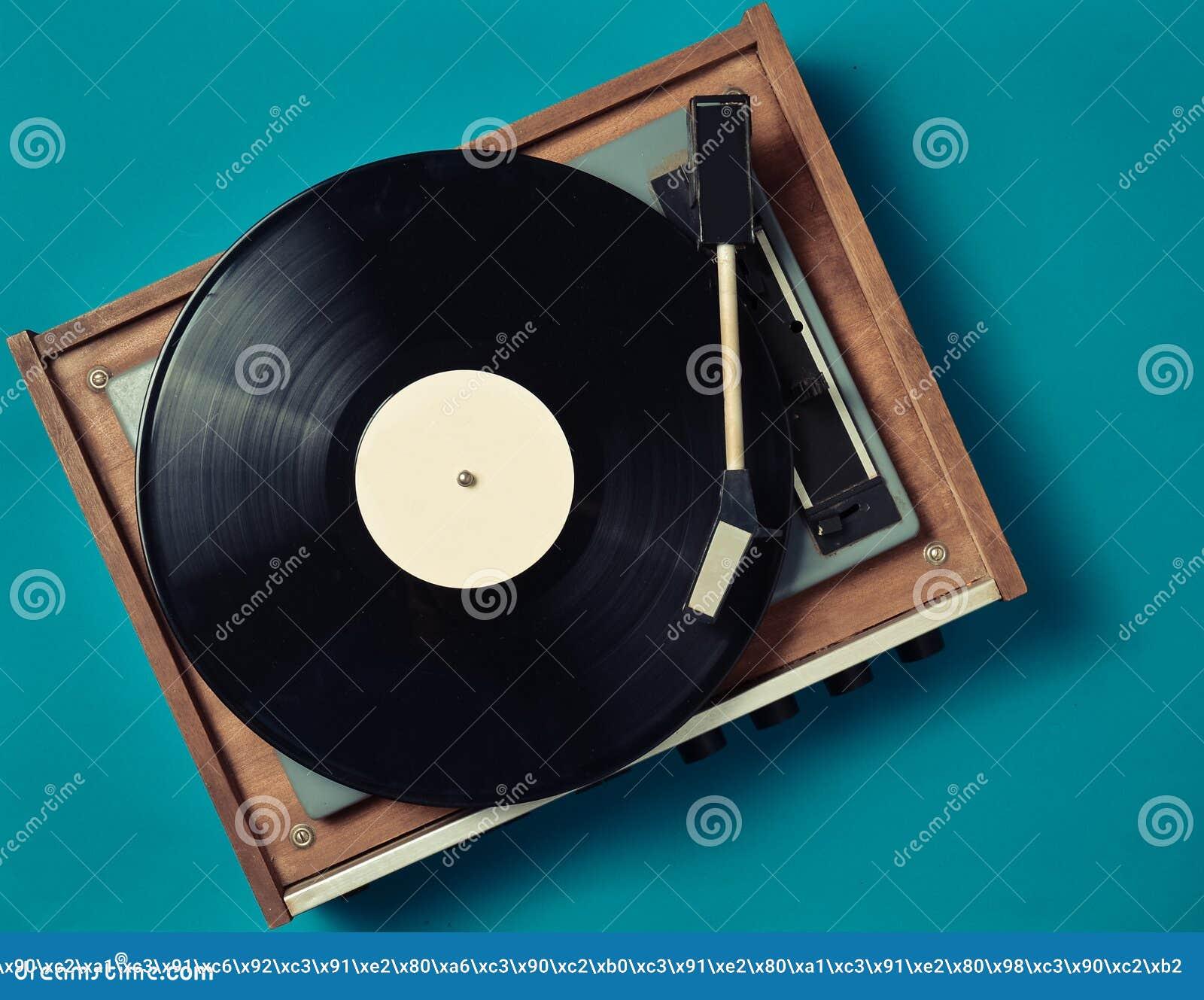 Retro vinyl player on a blue background. Entertainment 70s. Listen to music.