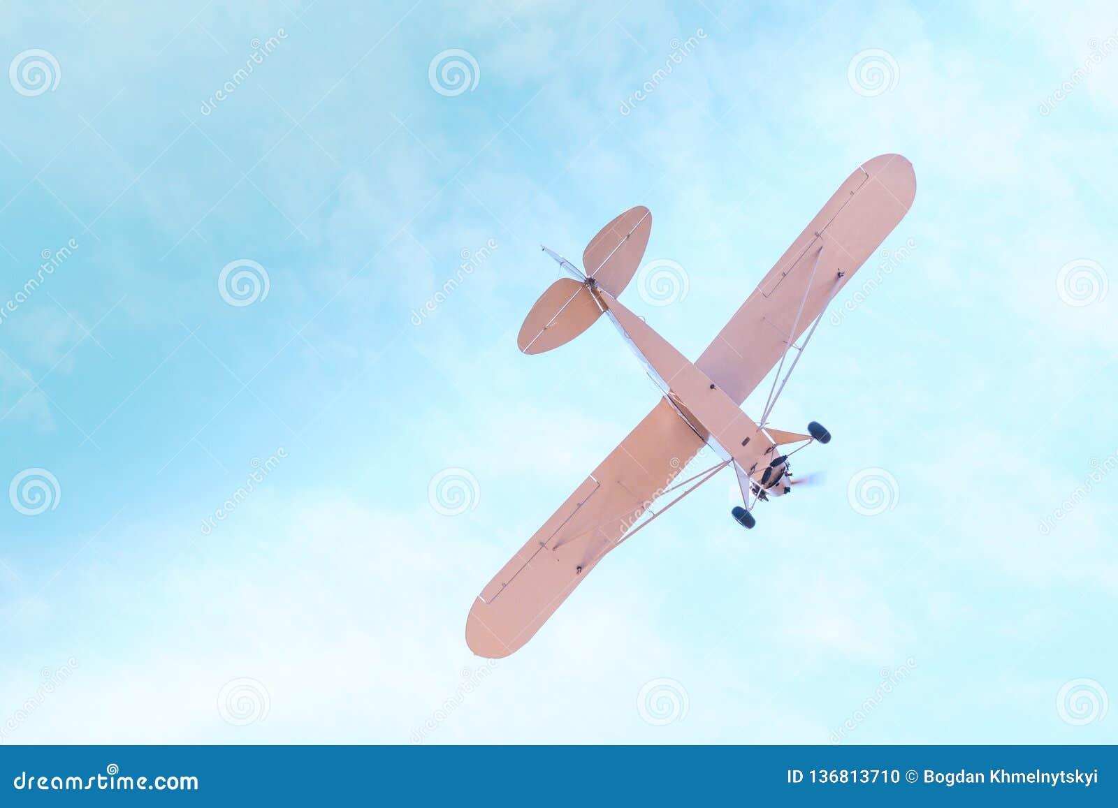 Retro vliegtuig met propeller het vliegen en duikvluchten tegen de blauwe hemel