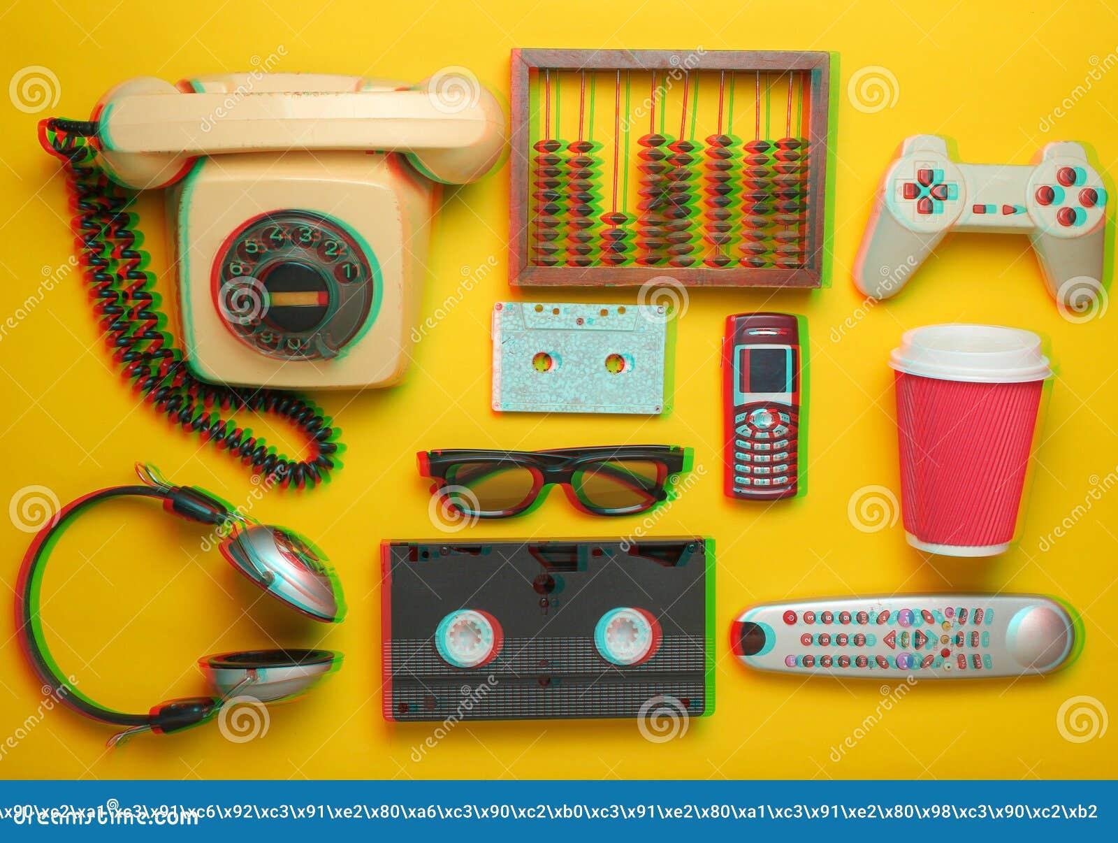 Retro voorwerpen op een gele achtergrond Roterende telefoon, audiocassette, videocassette, gamepad, 3d glazen