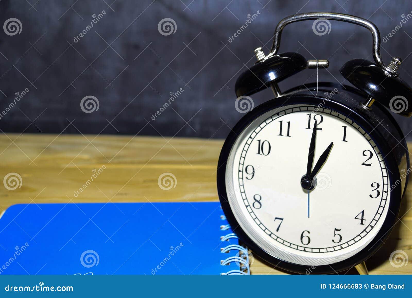 Retro- Wecker des Konzeptweinlesehintergrundschwarzen auf 13 00 P.M. oder 01 00 morgens und blaues Buch