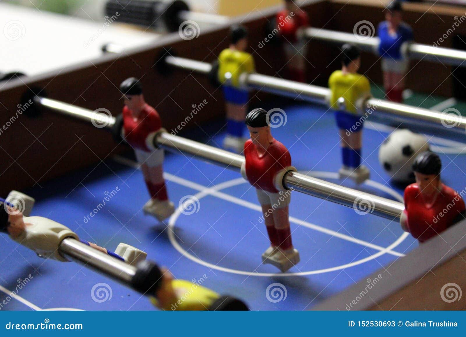 Retrocesso do jogo de futebol do futebol da tabela jogadores de equipe dos esportes em t-shirt vermelhos e amarelos