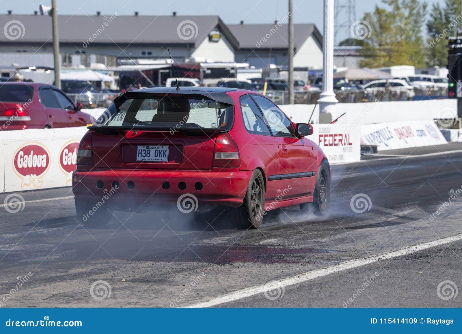 Retrovisione dell automobile di Honda sulla pista che fa un burnout