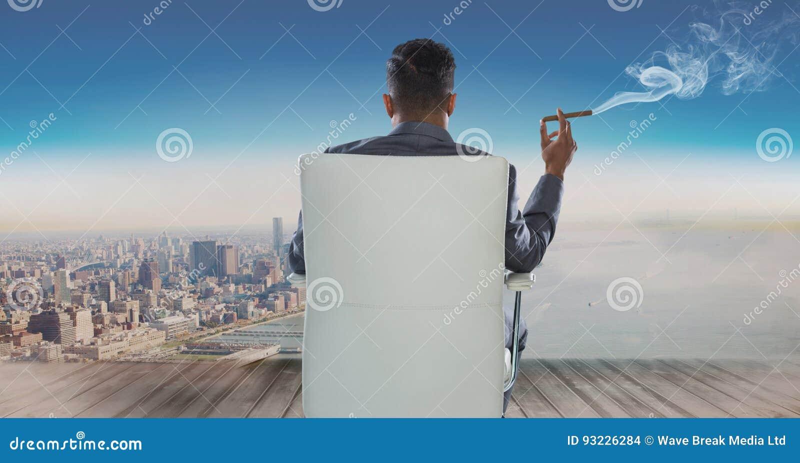 Retrovisione dell uomo d affari che si siede sulla sedia e che esamina mare mentre fumando sigaro