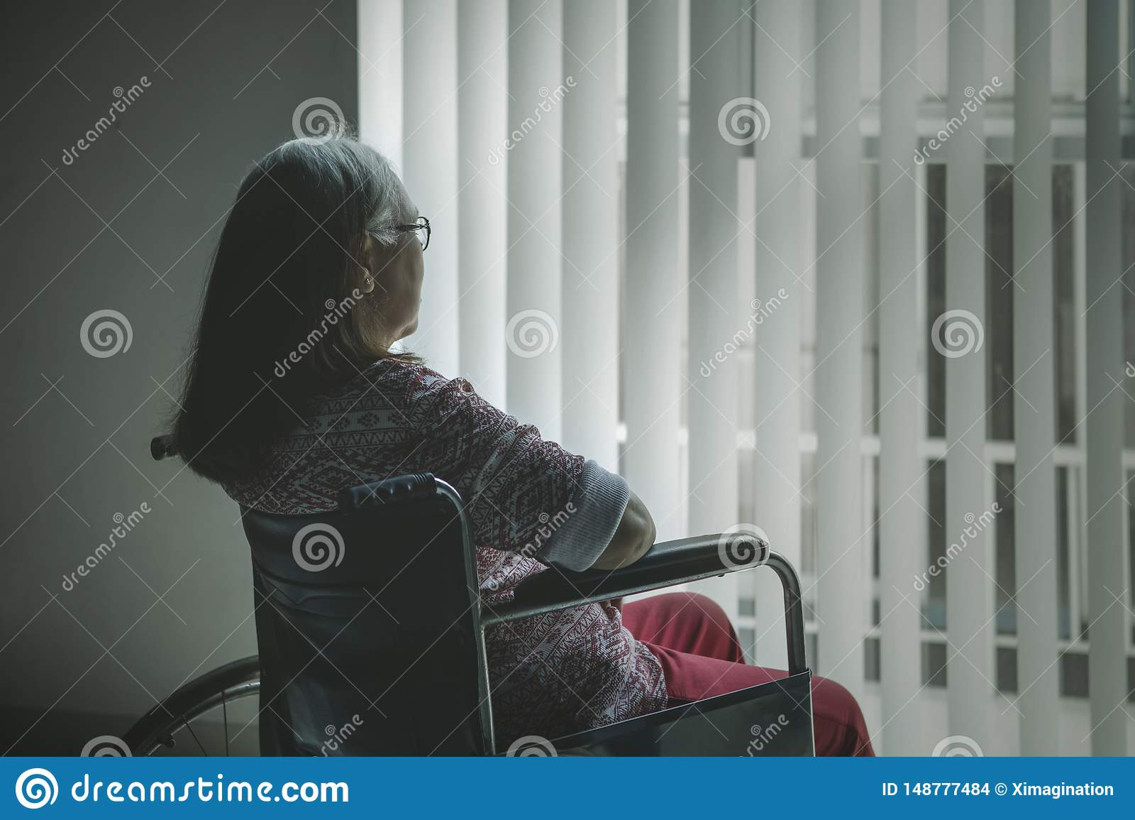 Retrovisione della donna invecchiata che guarda fuori la finestra