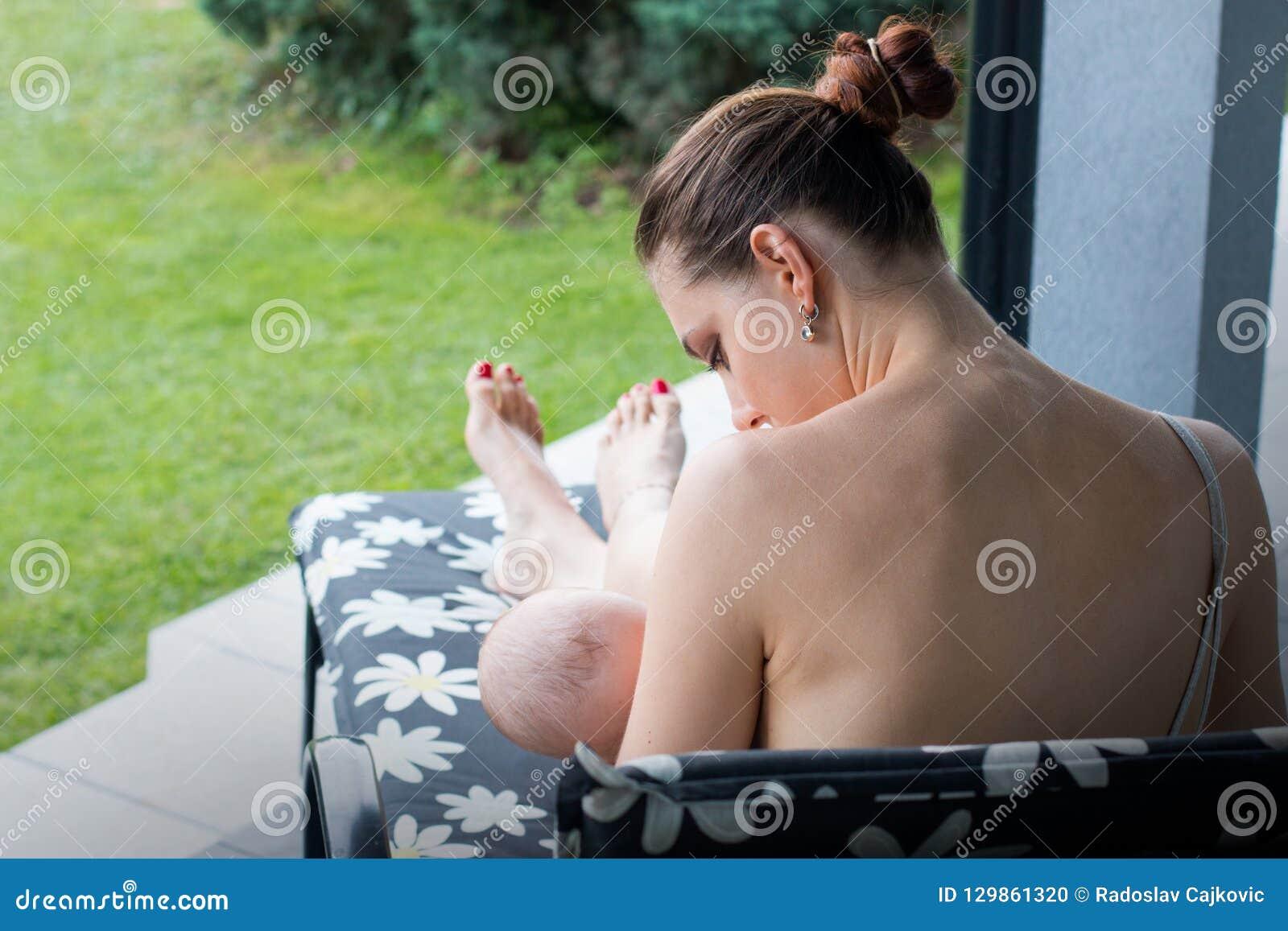 Retrovisione della giovane donna che allatta al seno piccolo bambino, curante un bambino sul portico
