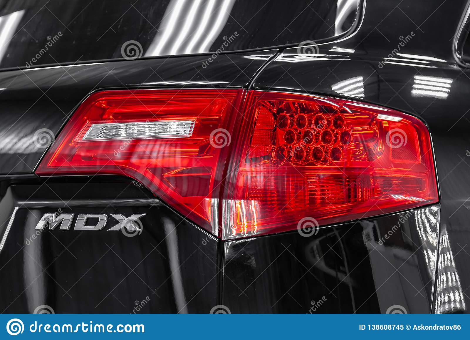 Retrovisione di Acura usato MDX colore del nero di 2008 anni con i fanali posteriori rossi che stanno nella scatola di servizio l
