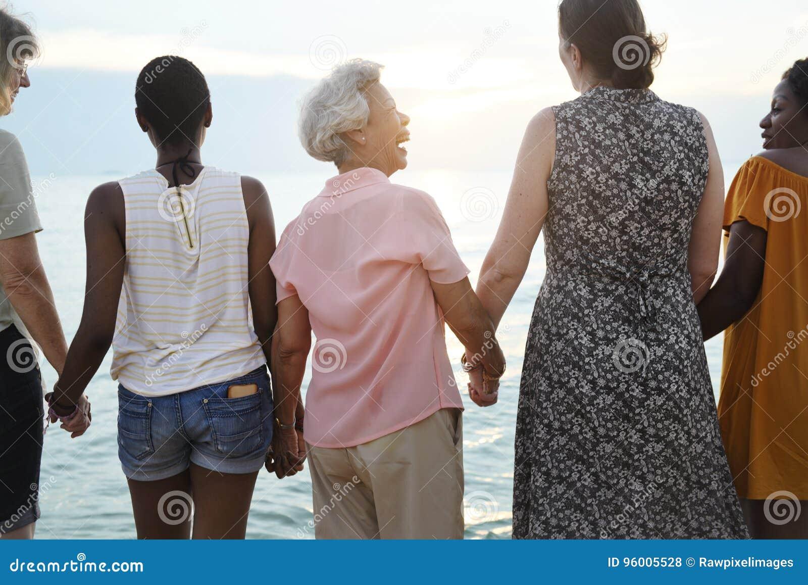 Retrovisione di diverse donne senior che si tengono per mano insieme al