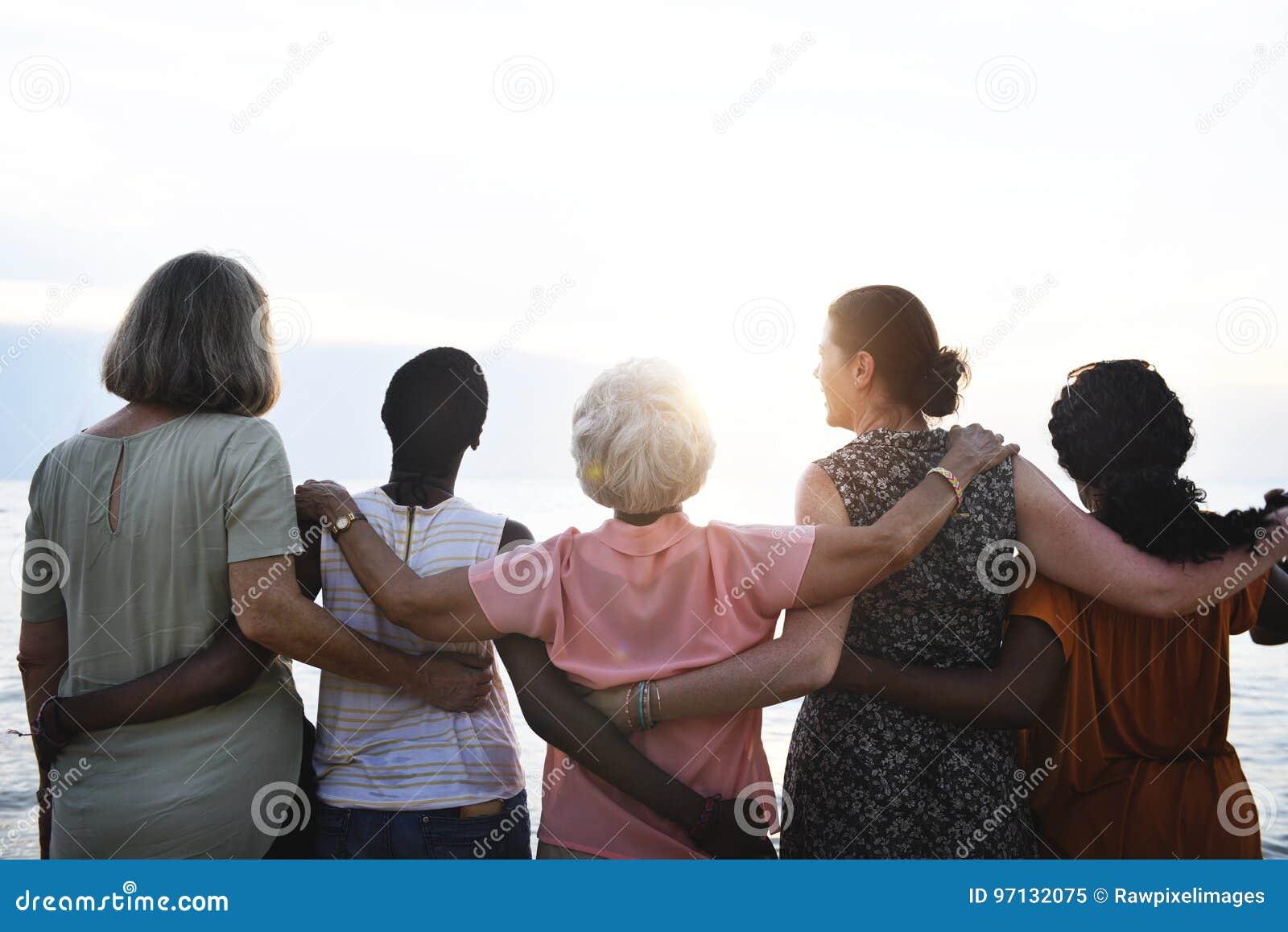 Retrovisione di diverse donne senior che stanno insieme alla spiaggia