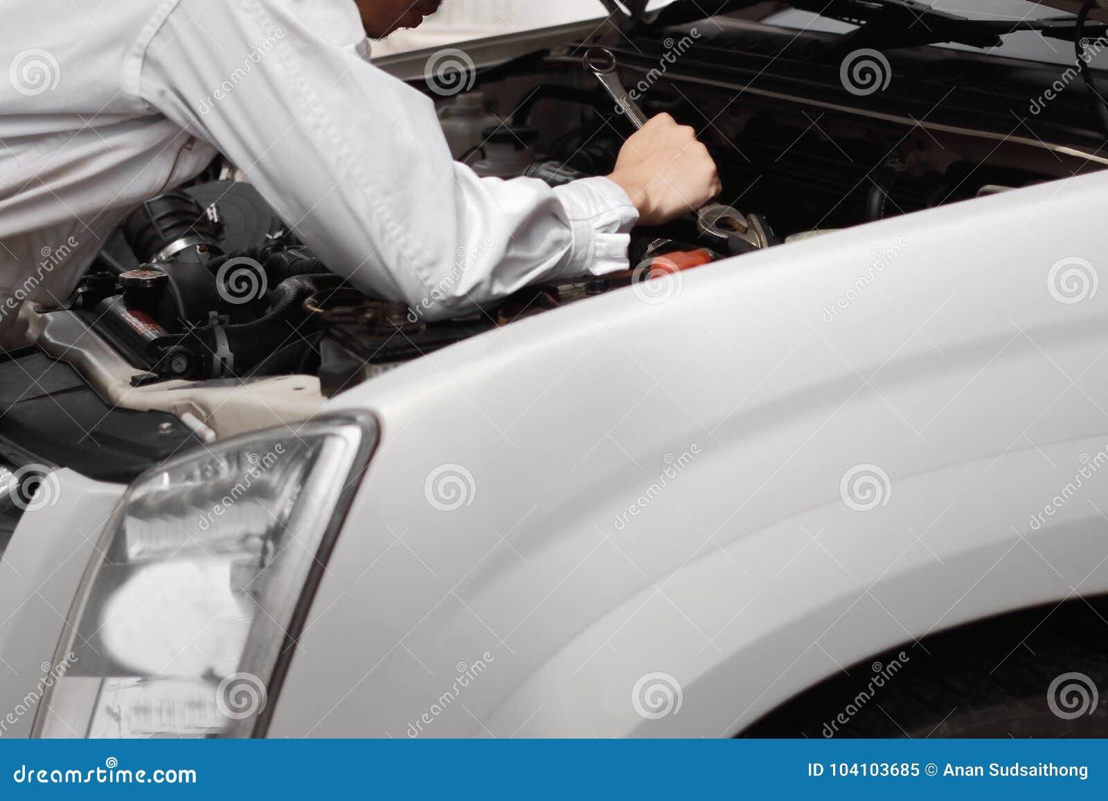Retrovisione di giovane uomo professionale del meccanico in uniforme con la chiave che diagnostica motore contro l automobile in