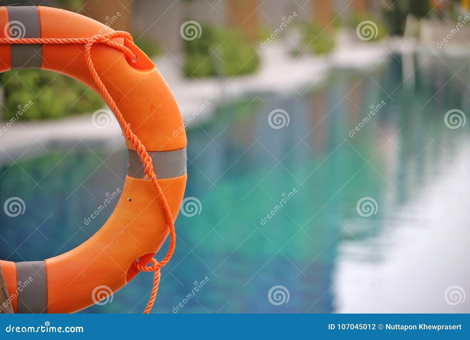 Rettungsring, Schwimmweste, Rettungsring, Rettungsgürtel, der am allgemeinen Swimmingpool im Unschärfehintergrund hängt Zu Konzep