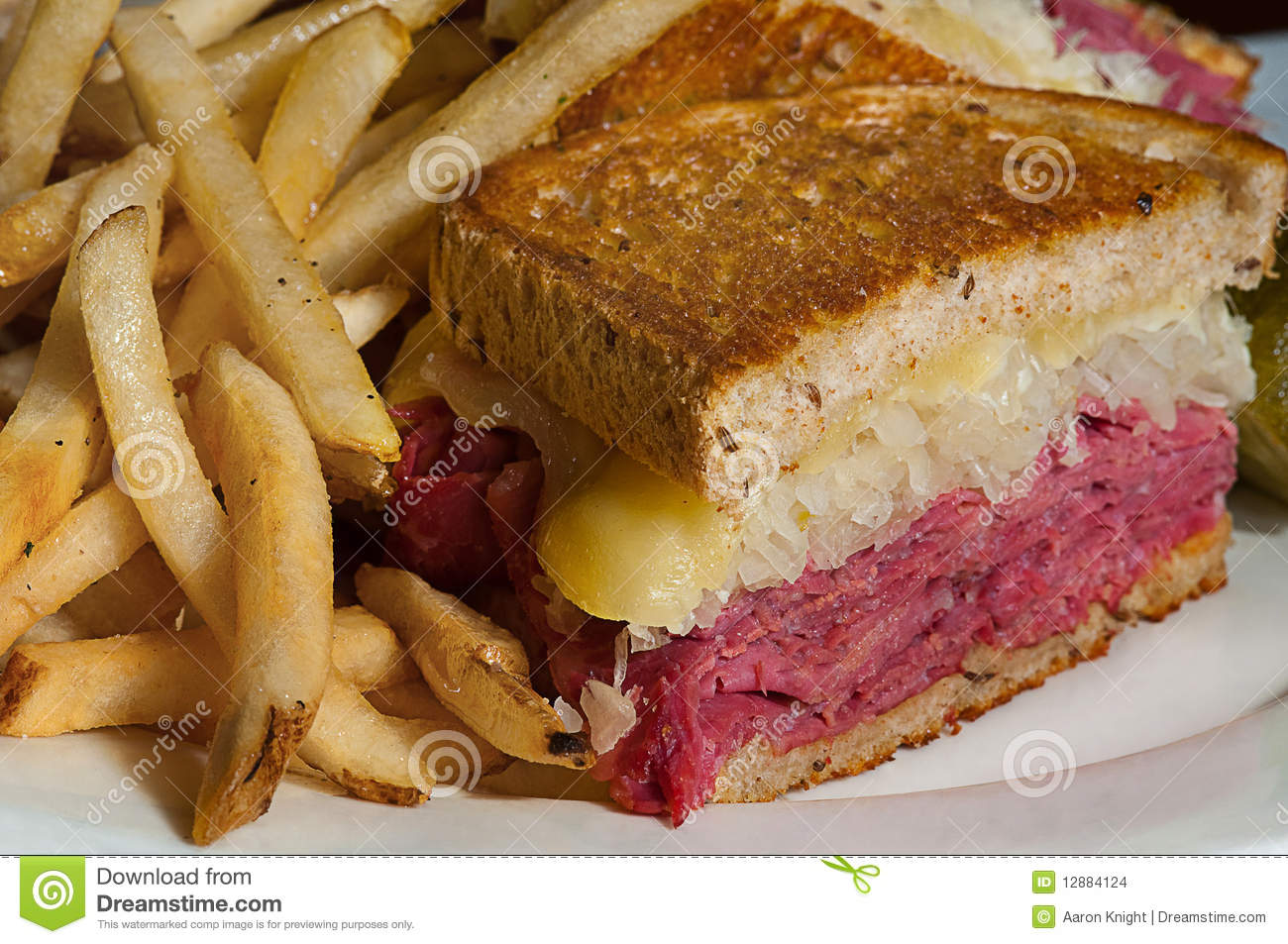Clean, tight shot of a freshly made Reuben sandwich with french fries ...