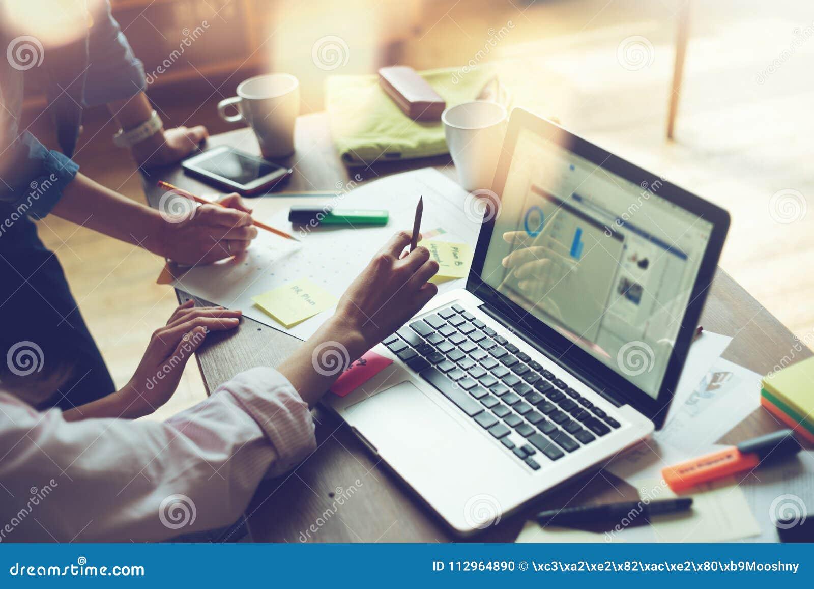 Reunião do projeto do negócio Equipe do mercado que discute o plano de funcionamento novo Portátil e documento no escritório aber