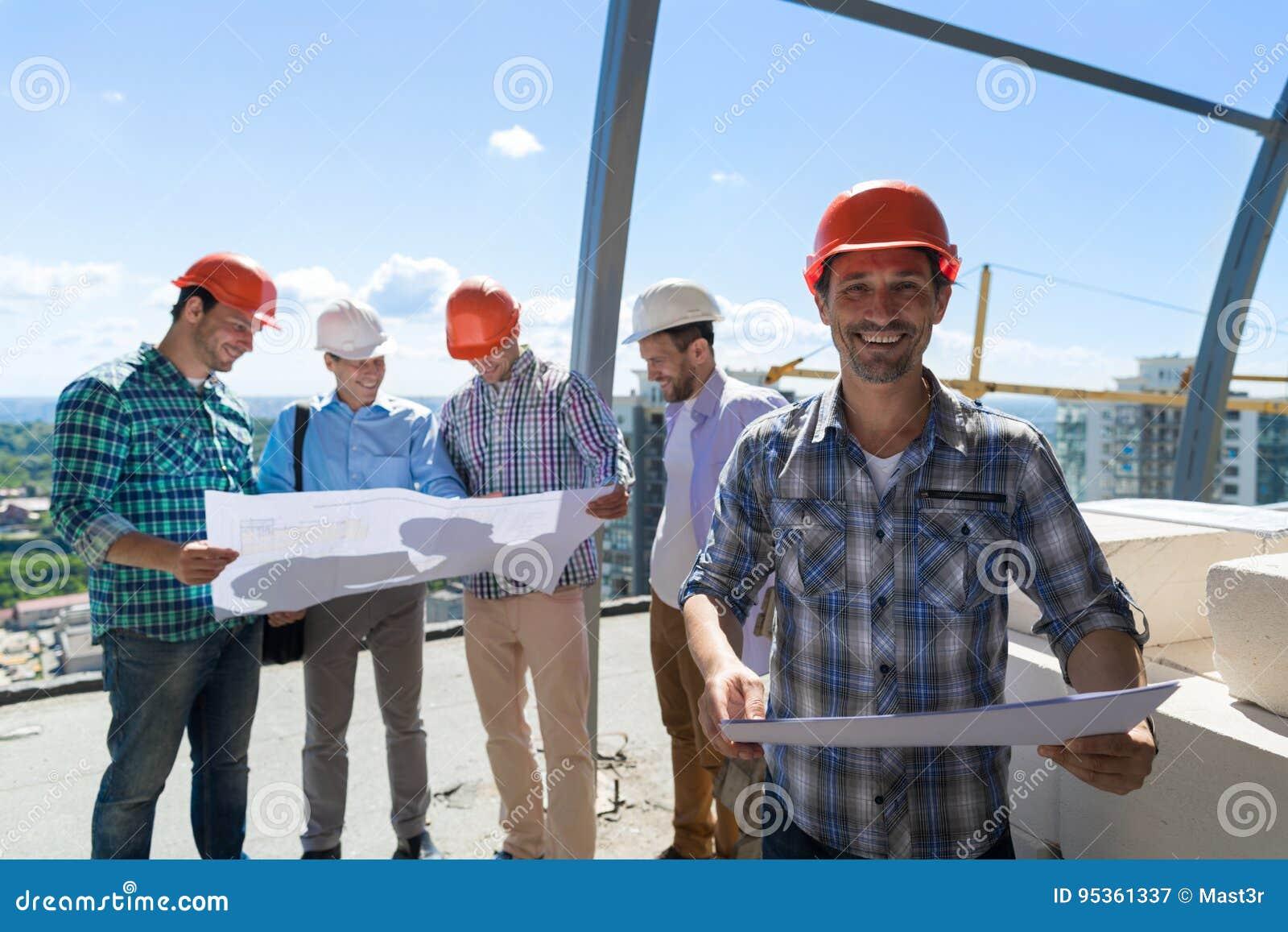 Reunião dos construtores Team Outdoors Group Of Foreman no capacete de segurança que olha o projeto de Duscussing dos planos com