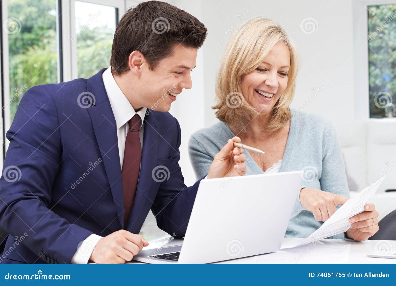 Reunião madura da mulher com conselheiro financeiro em casa