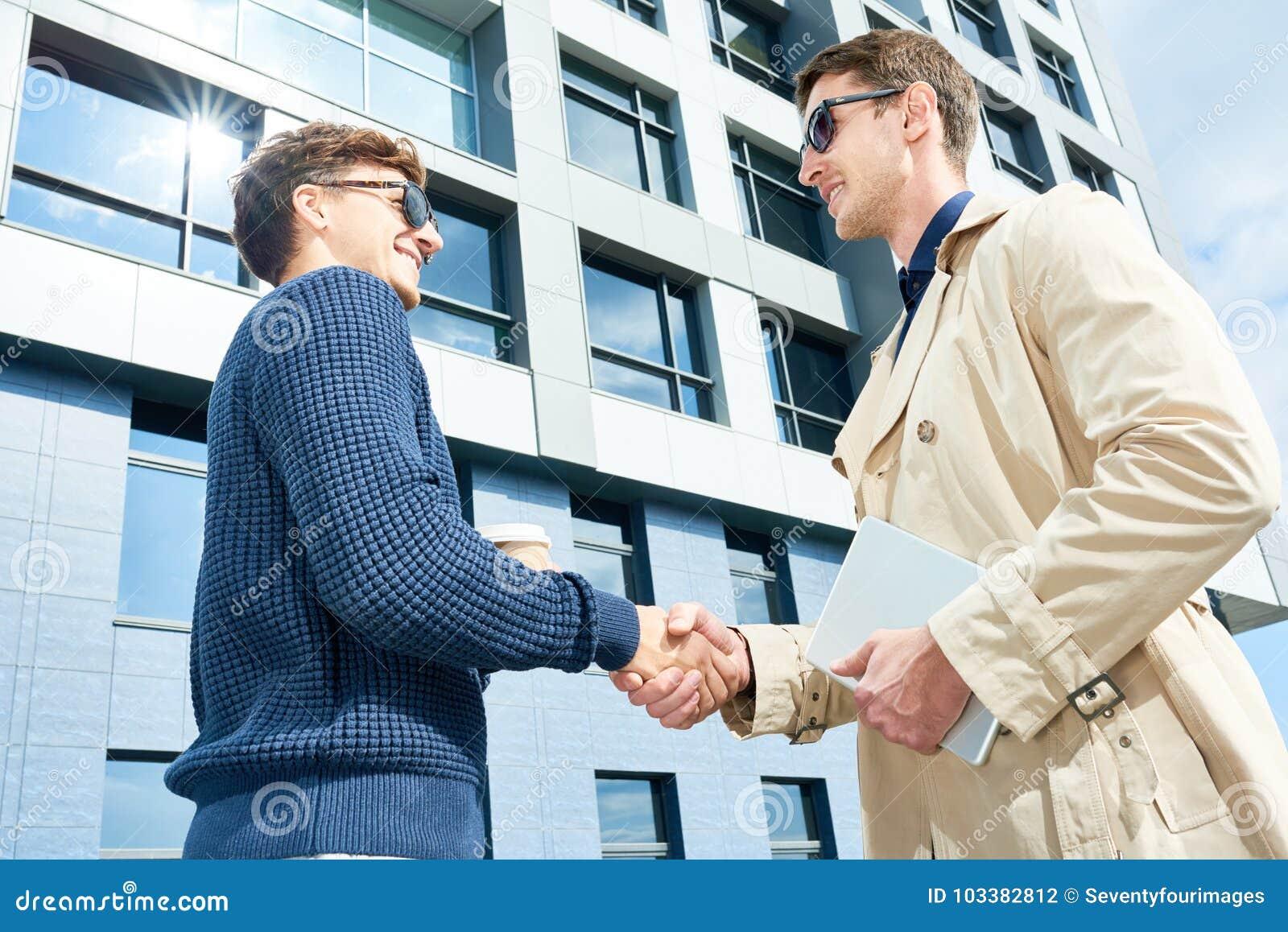 Reunión de dos empresarios al aire libre