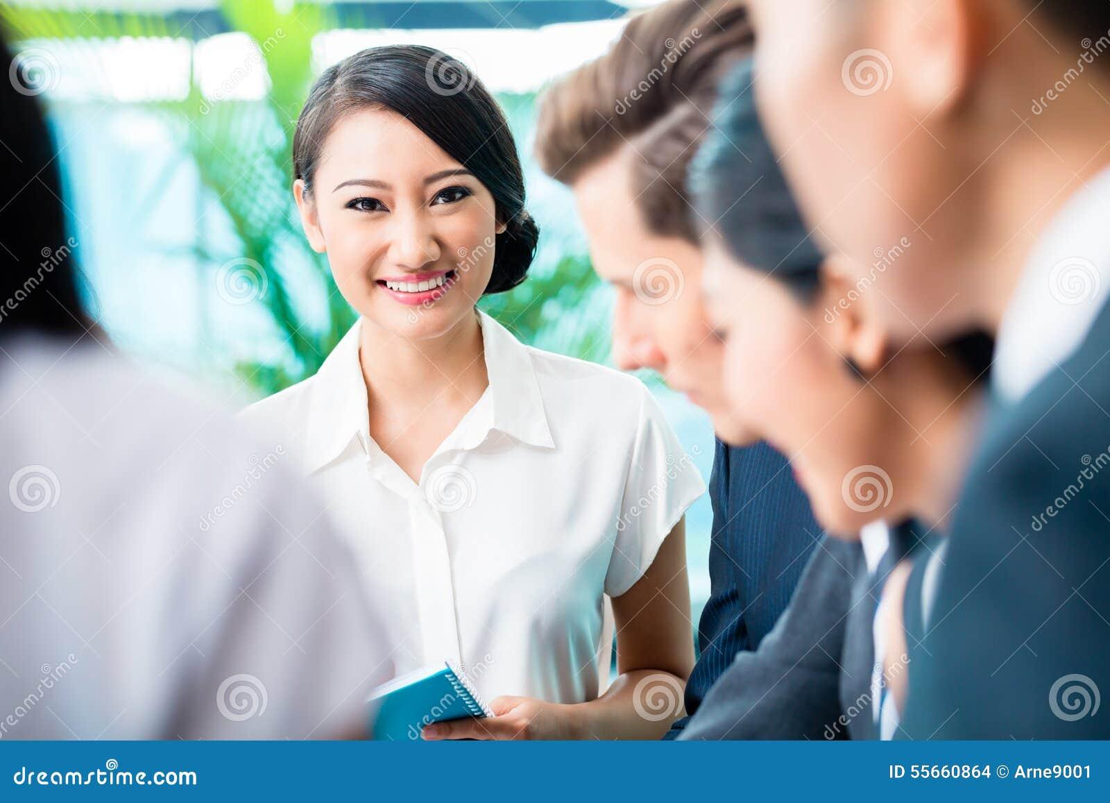 Reunión del equipo del negocio de ejecutivos asiáticos y caucásicos