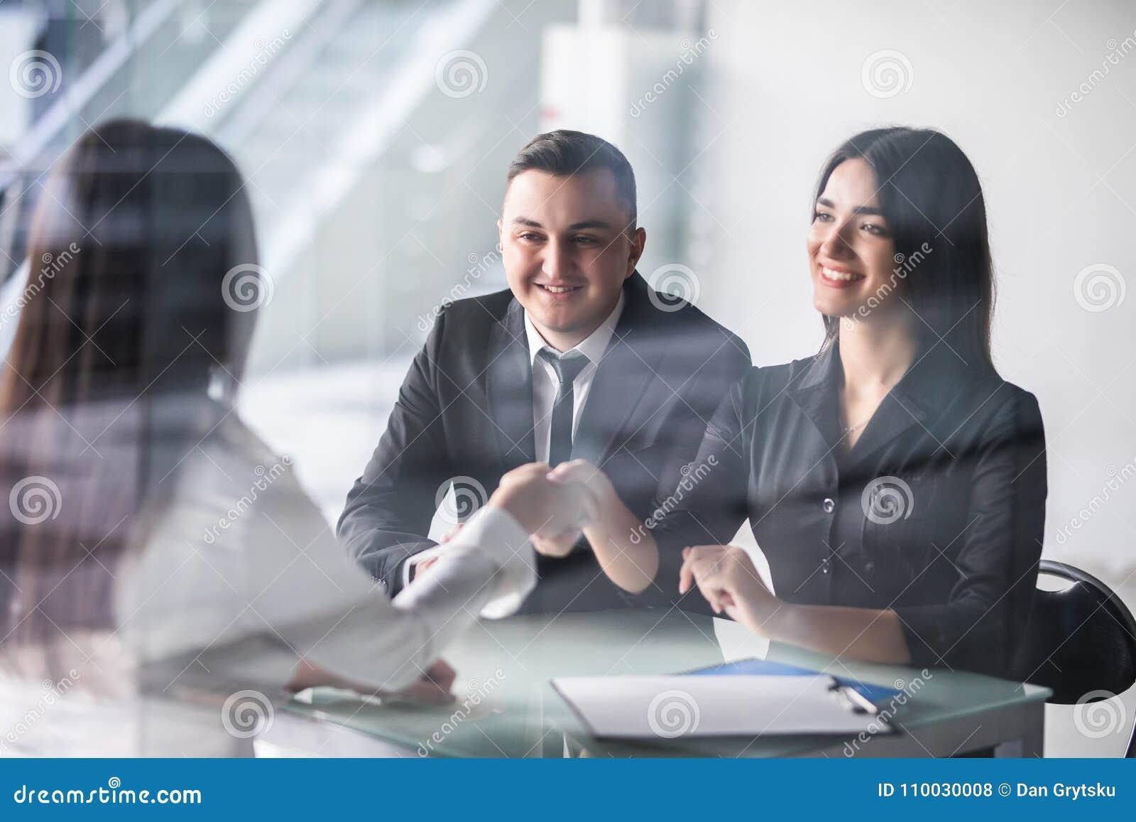 Reunión joven feliz de los pares con un agente en su oficina que se inclina sobre el escritorio para sacudir las manos, visión de