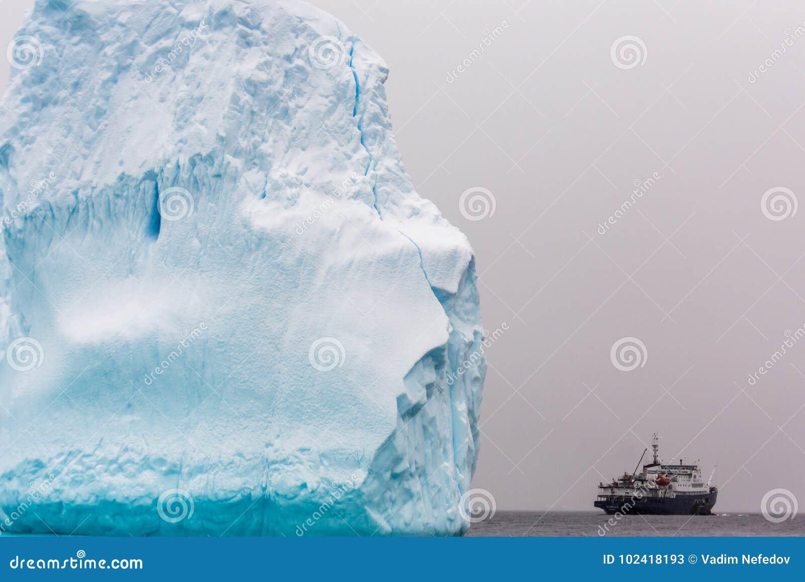 Reusachtig stuk van ijsberg met antarctisch cruiseschip bij de horizon,