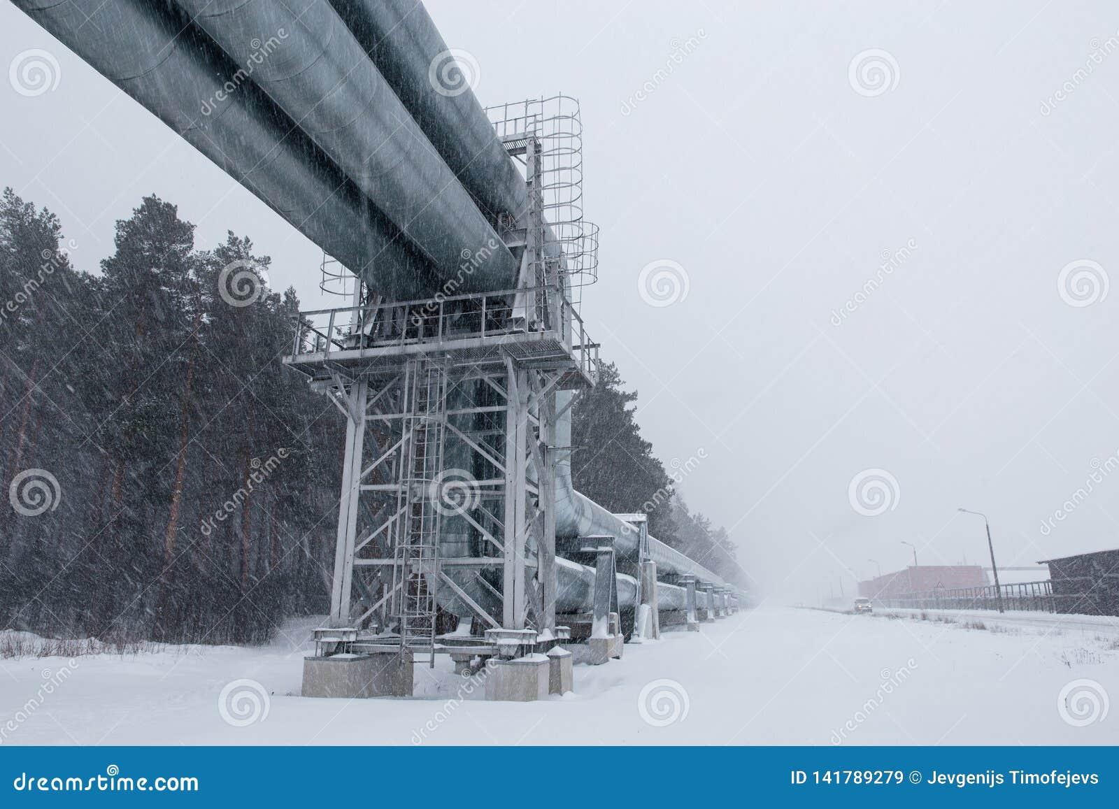 Reusachtige die aardgasleiding langs sneeuwstraat in Riga, Letland wordt gelegd