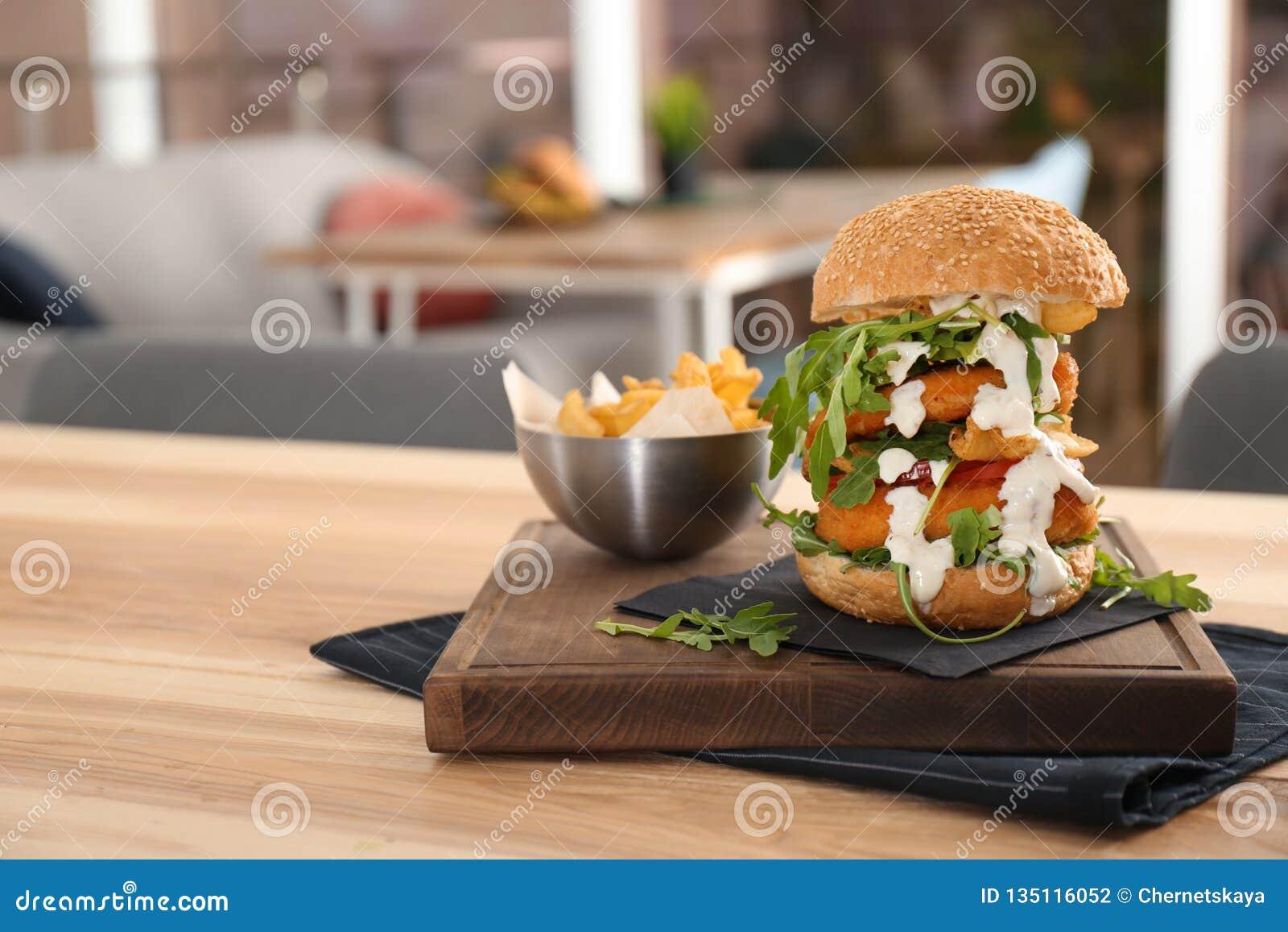 Reusachtige die yummy hamburger op lijst in koffie wordt gediend