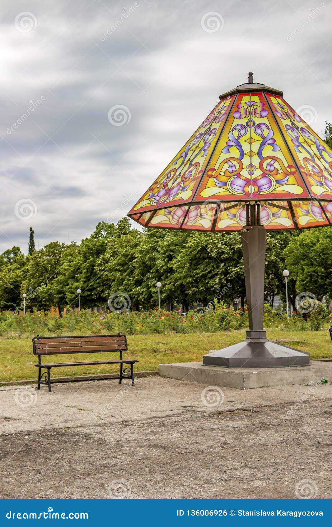 Reuzebedlamp en een bank in een openbaar park onder een donkere de zomerhemel