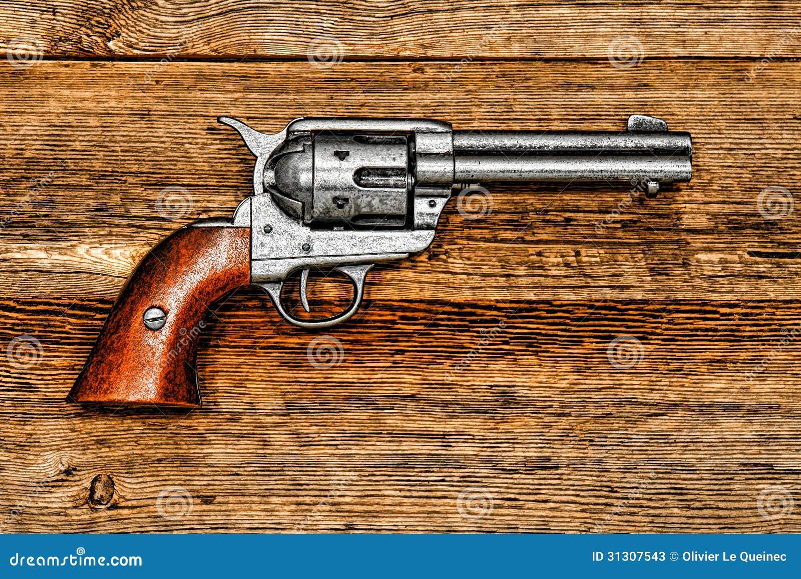 Revólver ocidental americano do pacificador da legenda na madeira