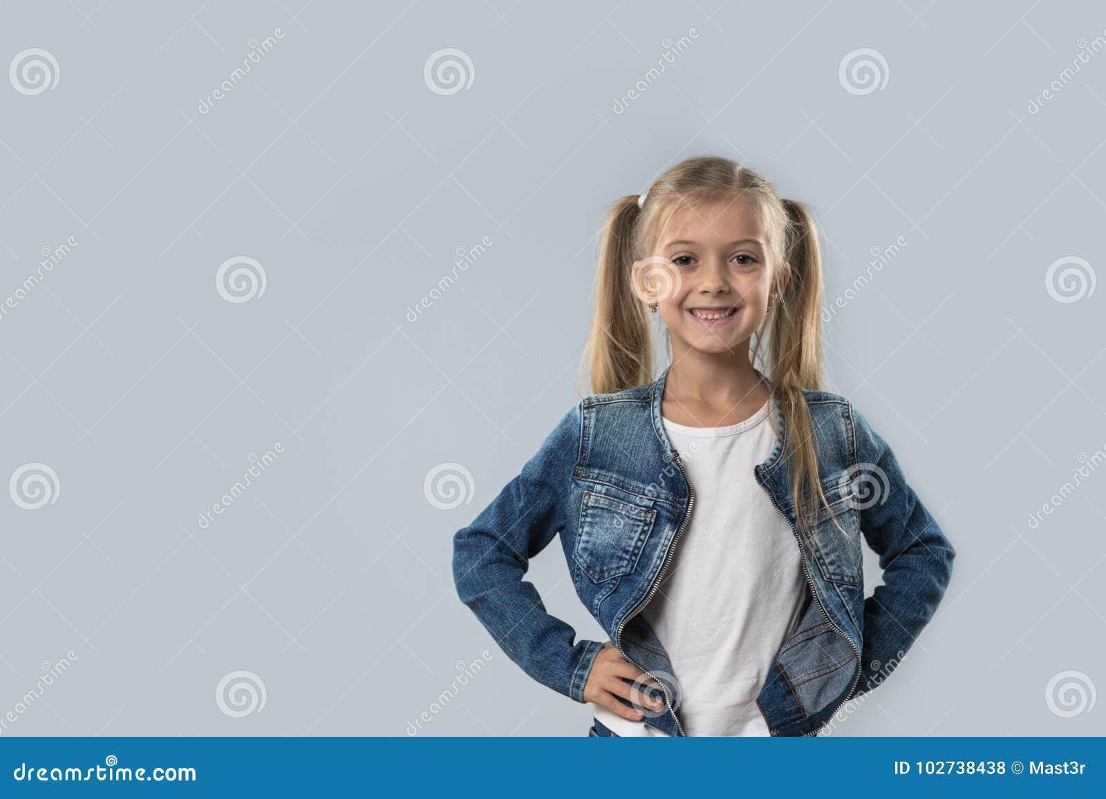 Revestimento de sorriso feliz das calças de brim do desgaste da menina bonita isolado