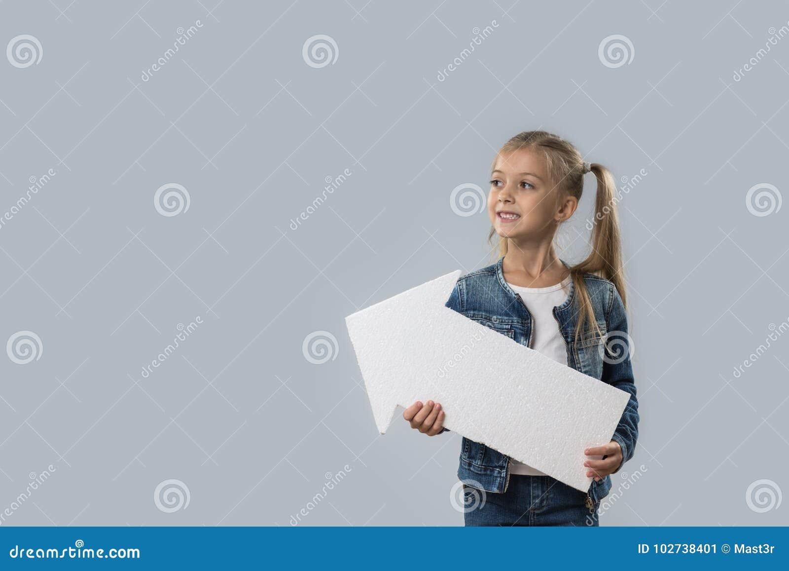 Revestimento de sorriso feliz das calças de brim do desgaste do espaço bonito da cópia da seta da posse da menina isolado