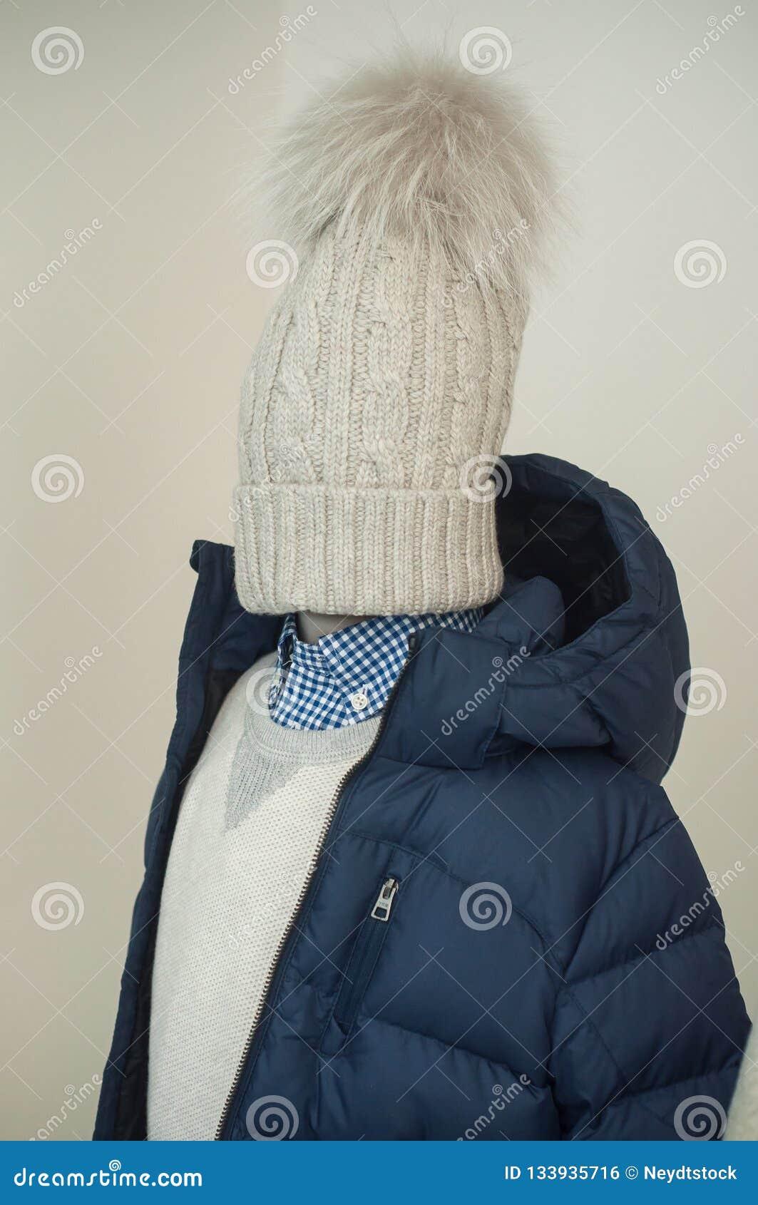 Revestimento do inverno e chapéu azuis de lãs no manequim na sala de exposições da loja da forma