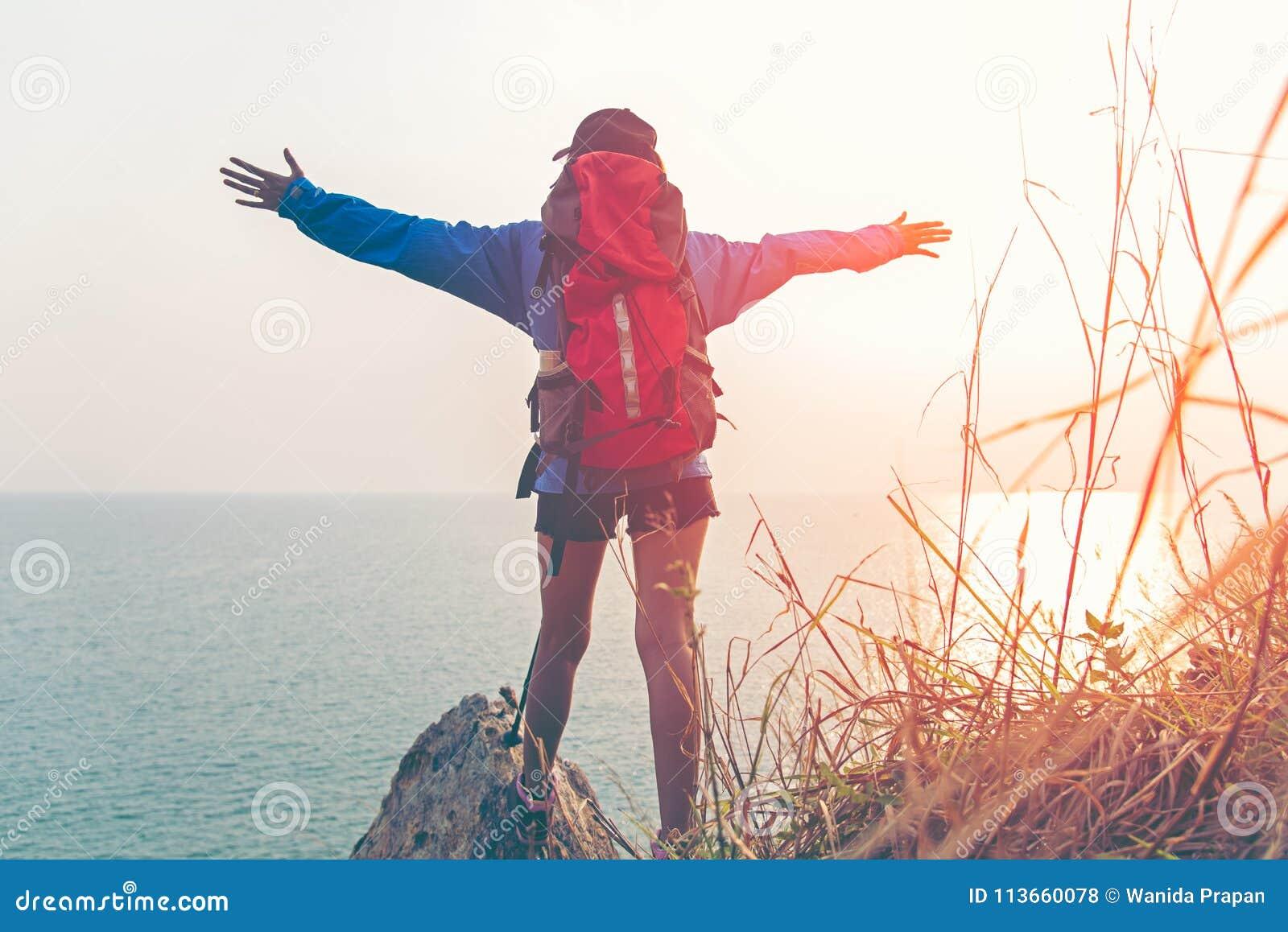Revestimiento victorioso del peso bueno y fuerte de la libertad feliz de la sensación de la mujer del caminante en la montaña nat