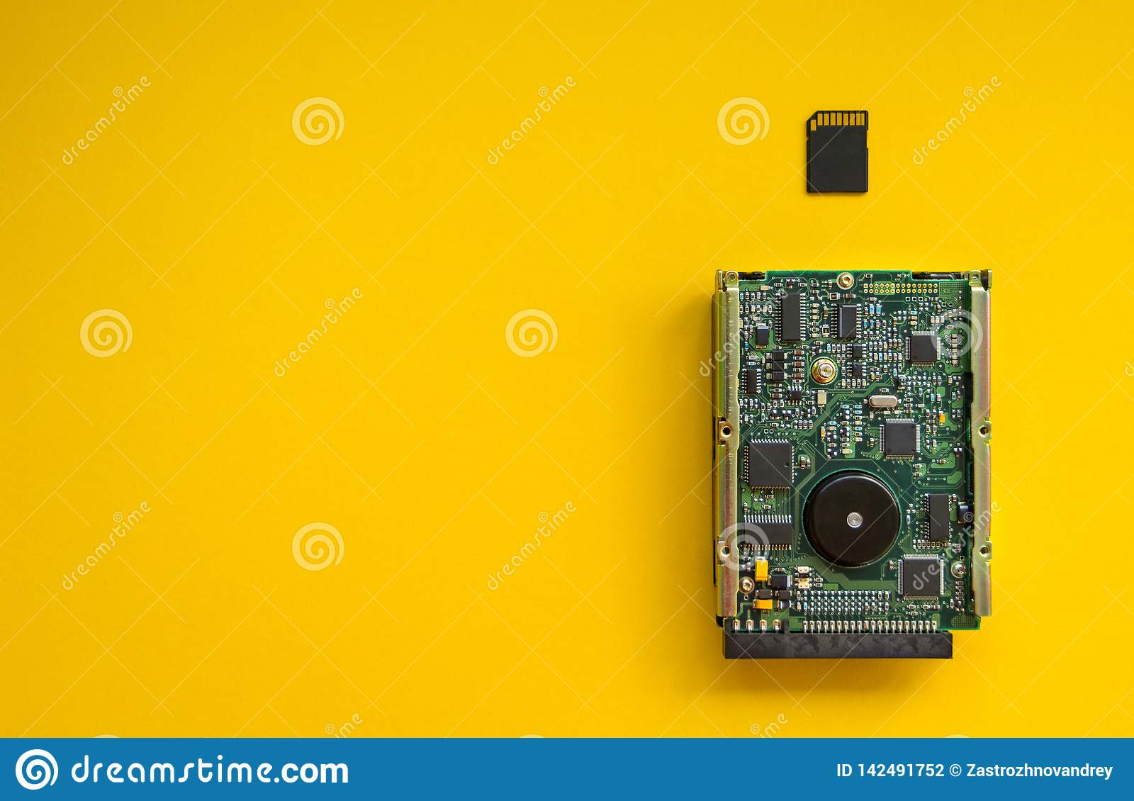 The revolution of technology memory devices on a yellow background, concept. The hard drive and memory card