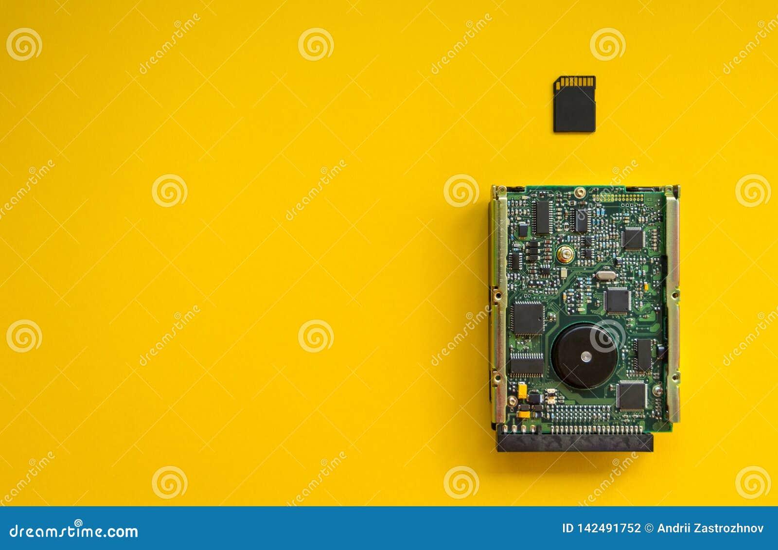 Revolutionen av teknologiminnesapparater på en gul bakgrund, begrepp Hårddisk- och minneskortet