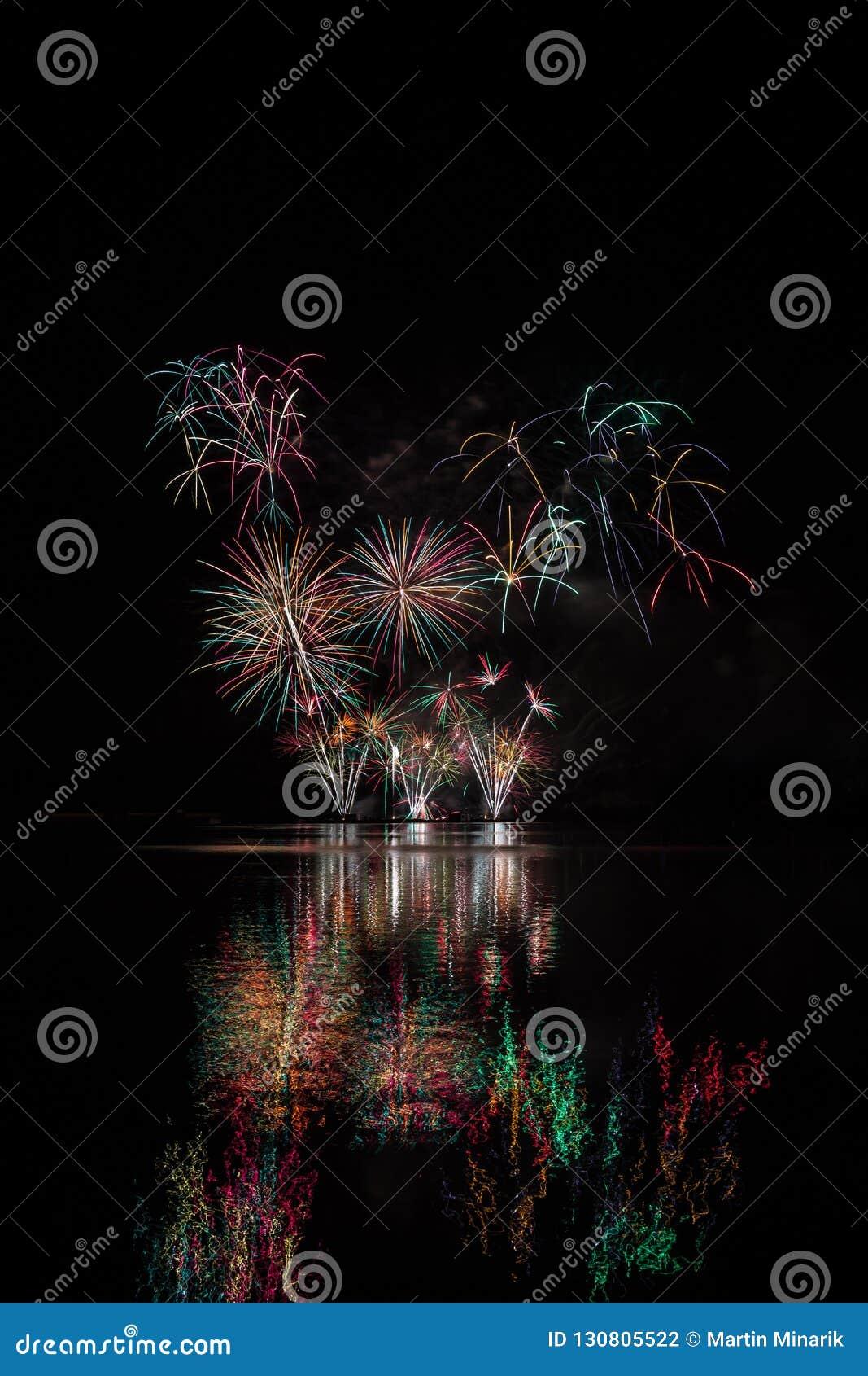 Rewolucjonistki, zieleni i koloru żółtego gwiazdy od bogatych fajerwerków nad Brno tamą z jeziornym odbiciem,