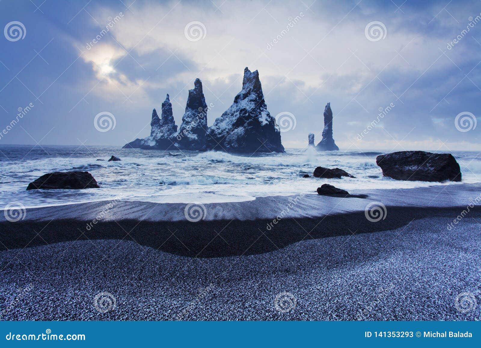 Reynisdrangar es pilas volcánicas del mar del basalto situadas debajo de los acantilados de la montaña Reynisfjall cerca del pueb