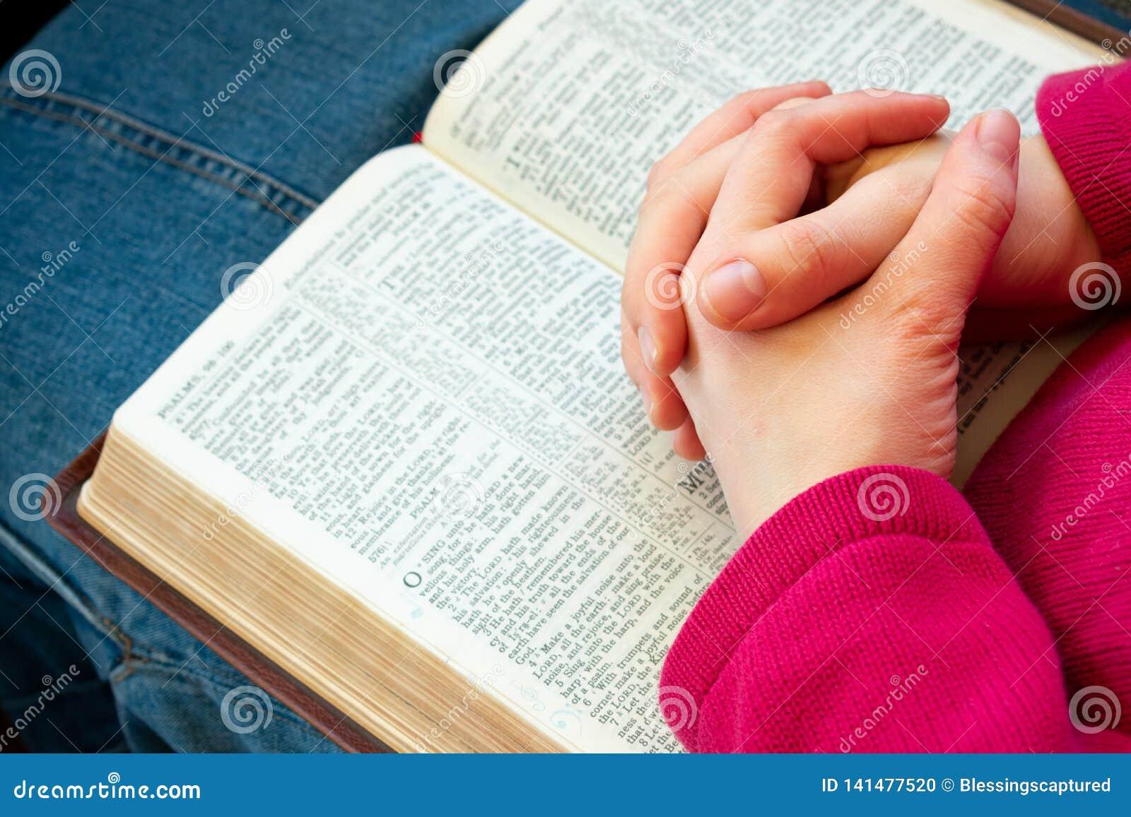 Rezando e lendo a Bíblia foto de stock. Imagem de saia - 141477520