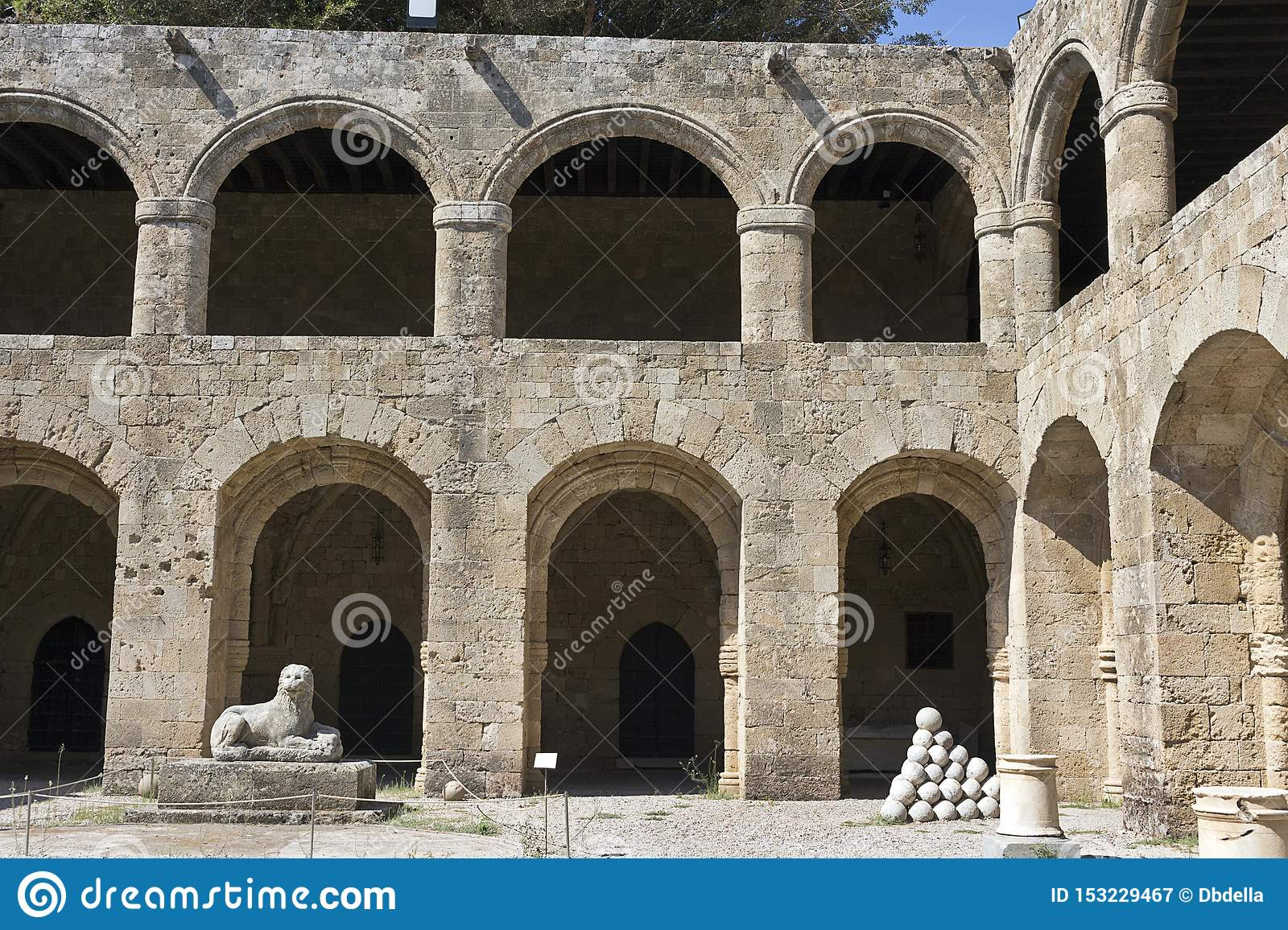 Rhodes Old City - Archaeological museum, old Hospital of the Knights. Courtyard surrounded by a galleries, lion statue and stacks