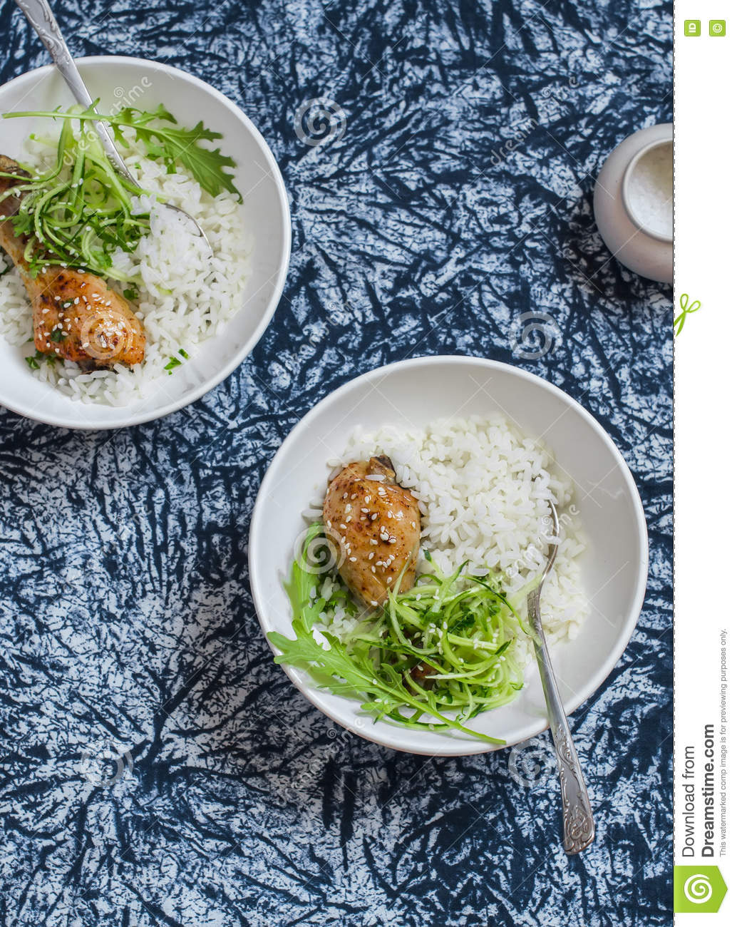 Rice, chicken and salad in a bowl on a dark background.