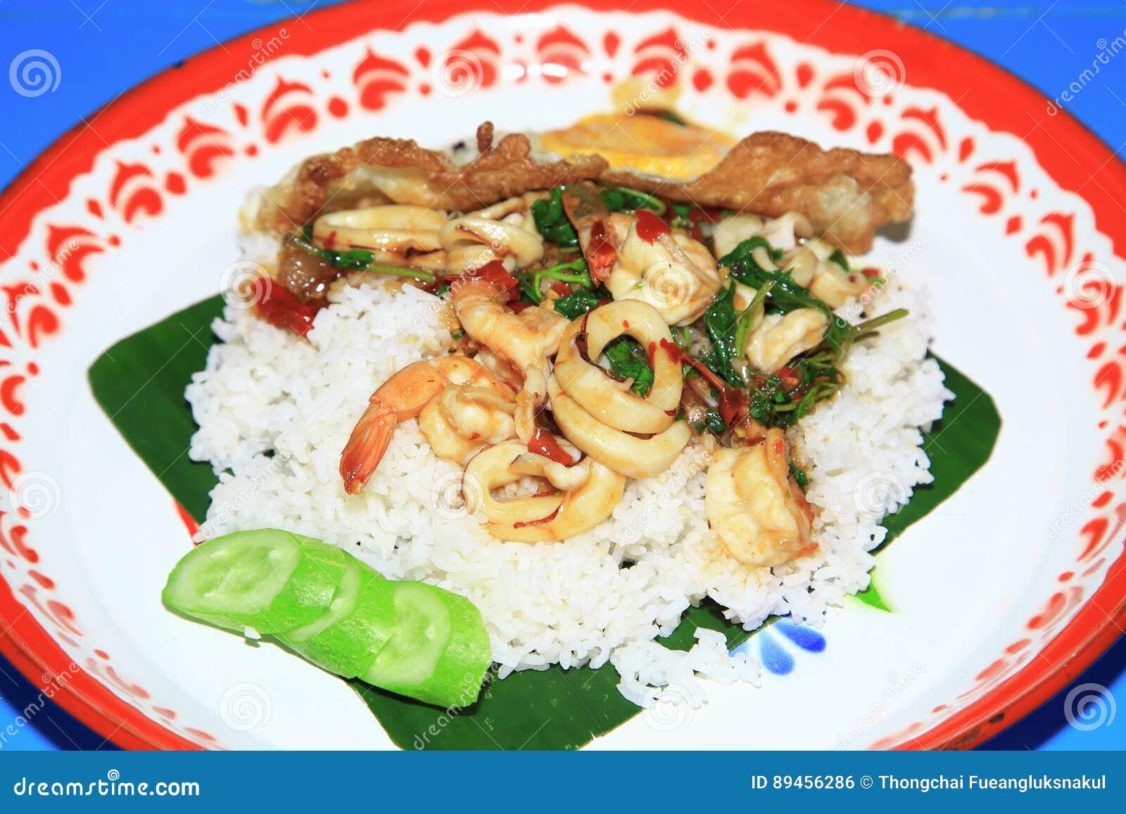 Rice nakrywał z smażącymi owocami morza i basil z Smażącym jajkiem w dużej tacy, Tajlandzki język jest Kao ochraniaczem Kaprao Ta
