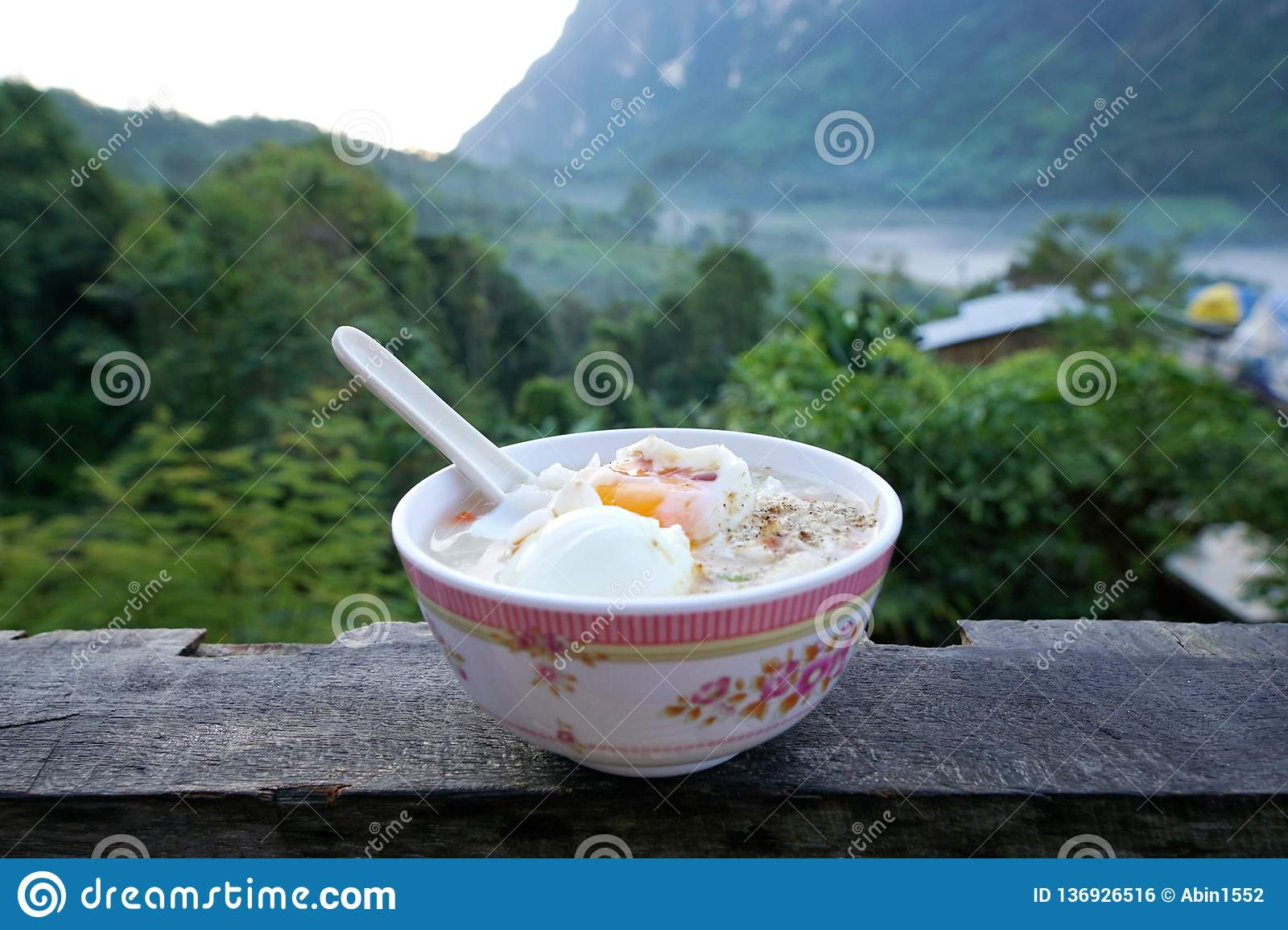 Rice porridge with parboiled egg, minced pork and pepper on wooden table, rice gruel or congee in forest.
