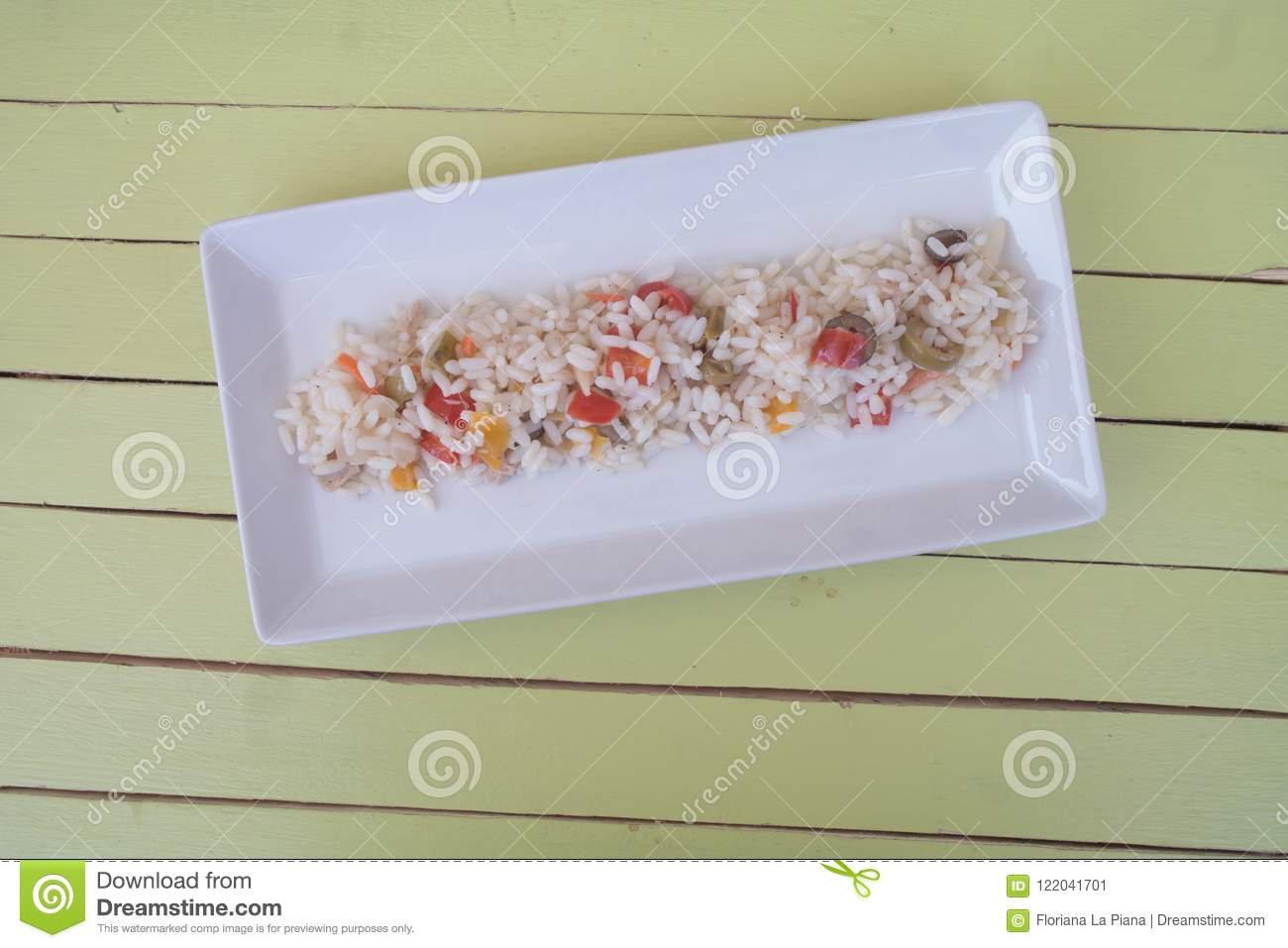 Rice salad in a white tray on green wood from above