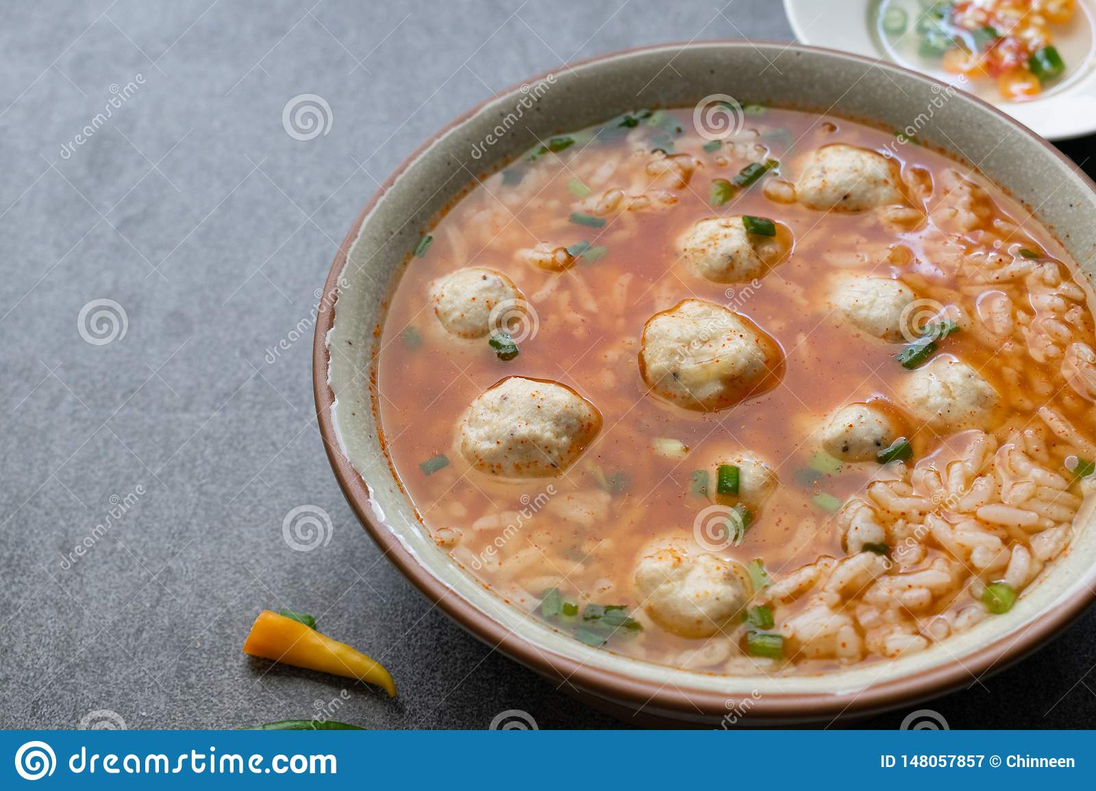 Rice spicy soup with chicken ball and chilli in gray bowl on table