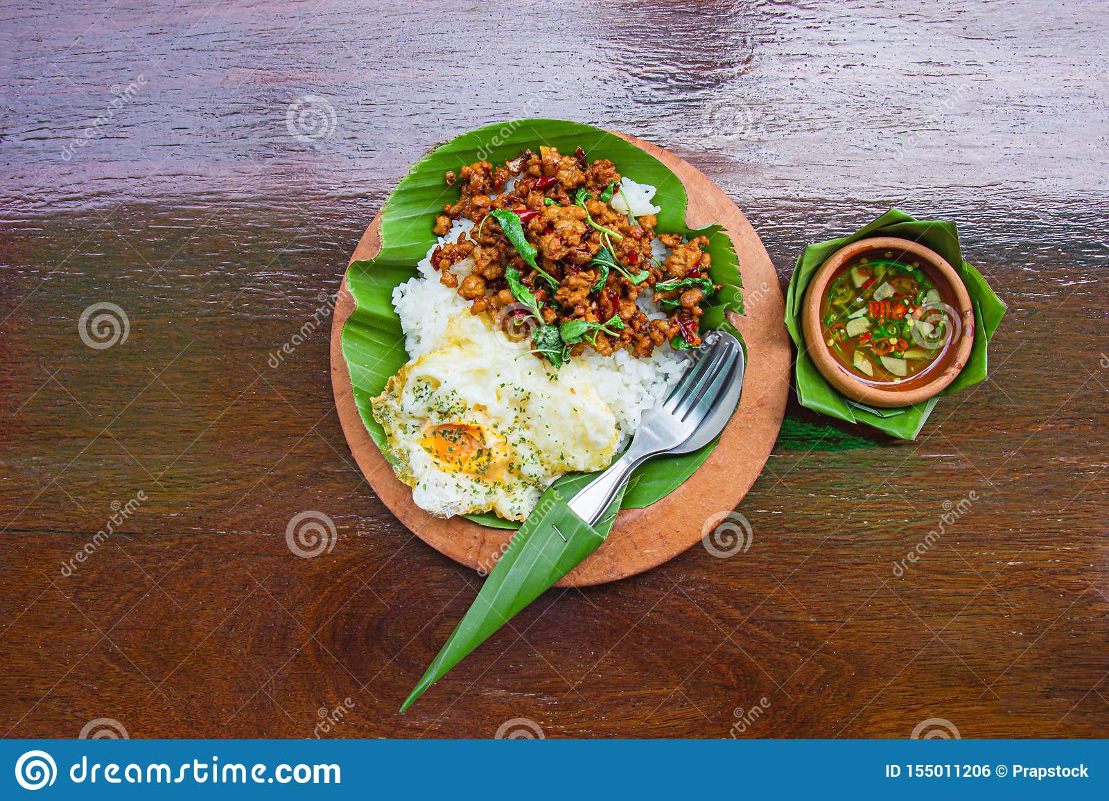 Rice topped with stir-fried minced pork and basil with Fried egg decorated with banana leaf and put on dark brown wood table. Top