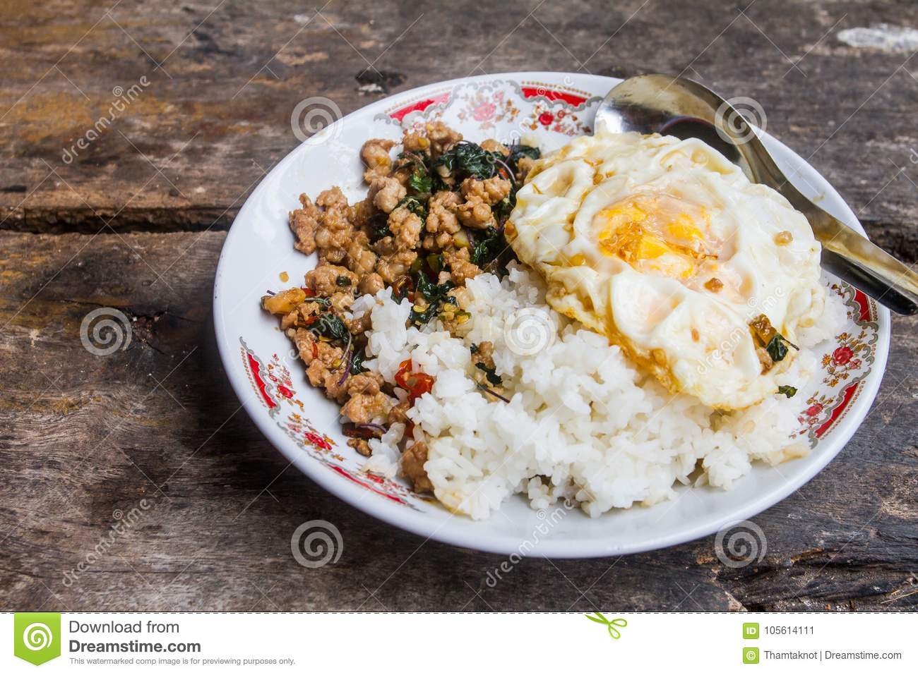 Rice topped with stir-fried pork with basil and fried Egg, placed on a wooden floor, which is the background.