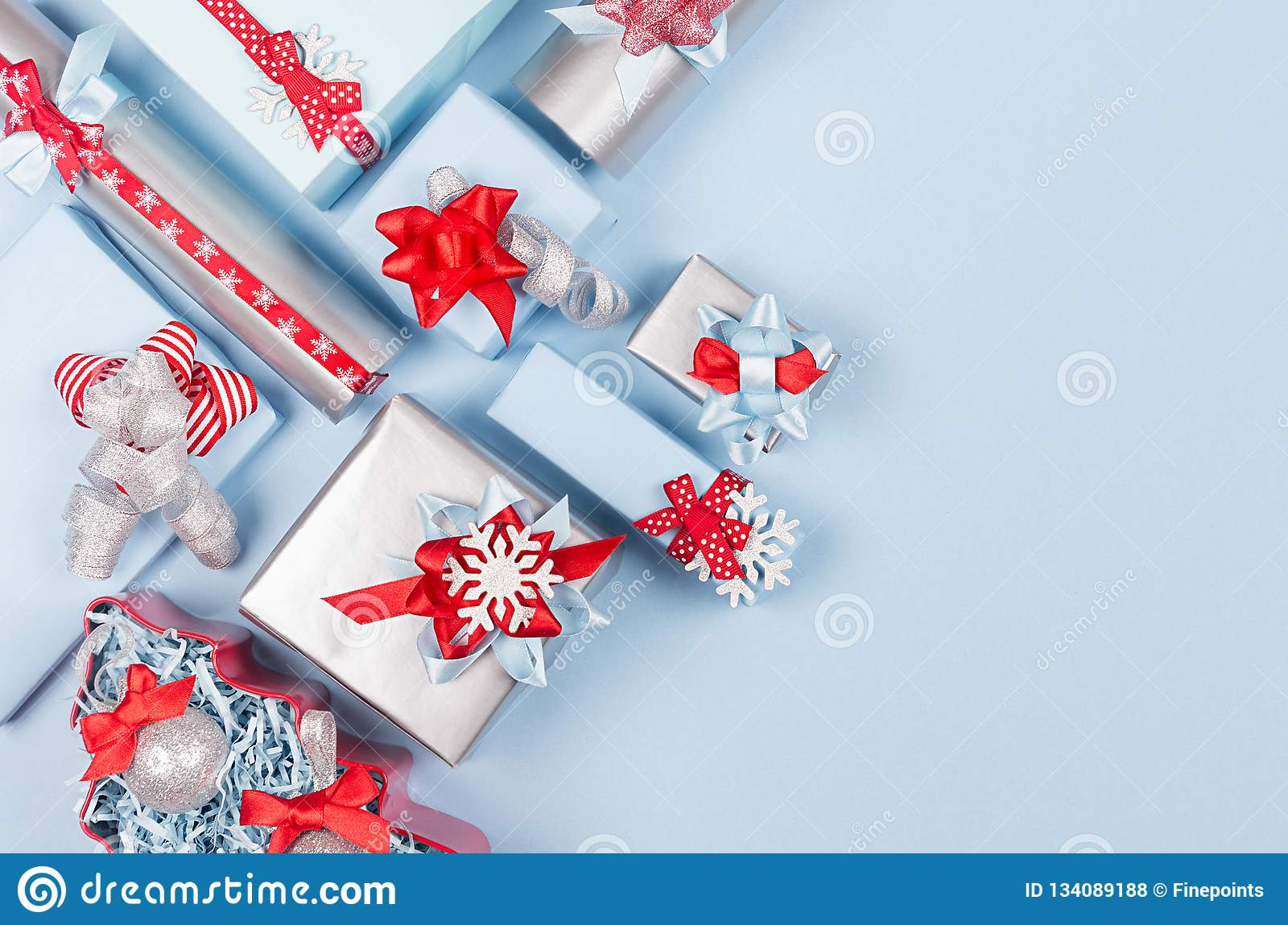 Rich bright winter season celebration background in red, pastel blue and silver color with different gift boxes.